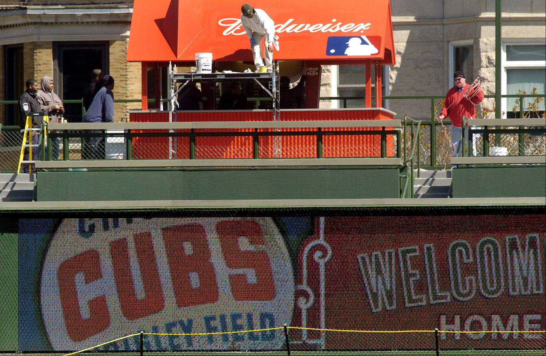 Workers put finishing touches to patio area in right field above a newly installed Jumbotron.