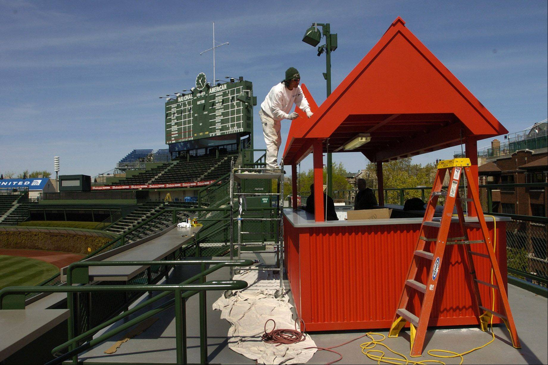 Dante Peralta paints the bar in the new patio area in right field.