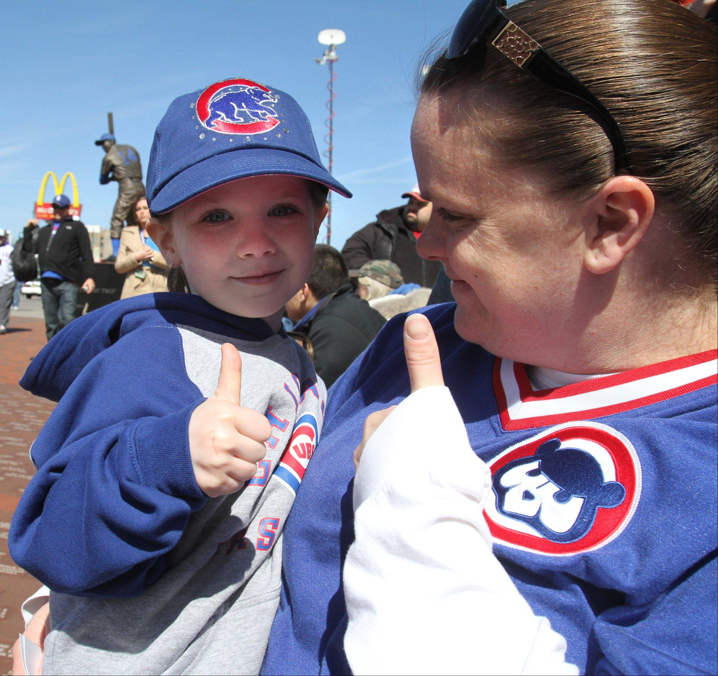 Amanda Tomasello of Bartlett and her daughter predict a good Cubs season in front of Wrigley Field on Opening Day Thursday.
