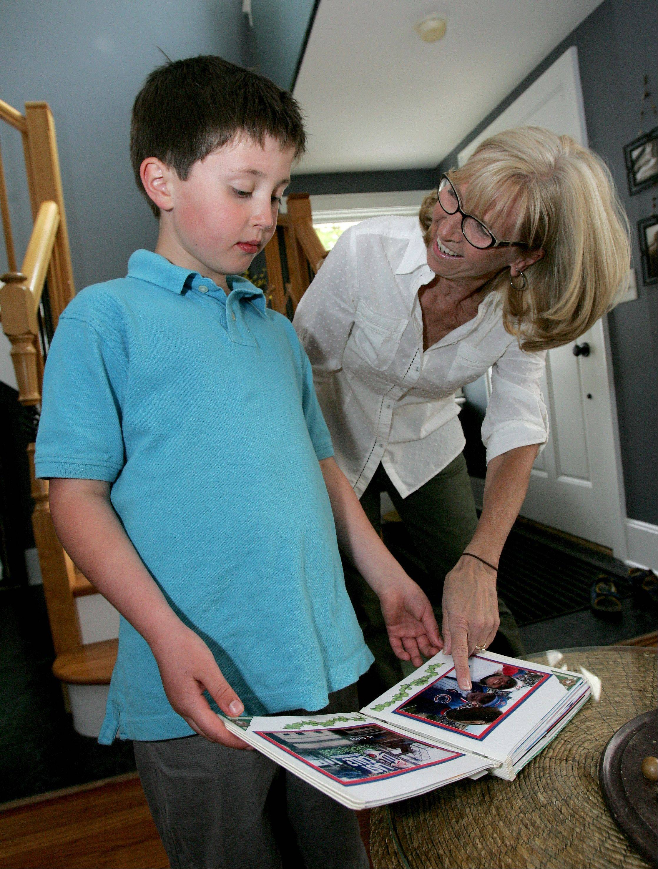 Showing her grandson Cal, 7, the family scrapbook of Cubs moments, Debra Hruby of Wheaton will be attending her 28th straight Opening Day at Wrigley Field today with Cal, Cal's father Sean of Geneva and her husband Mike.