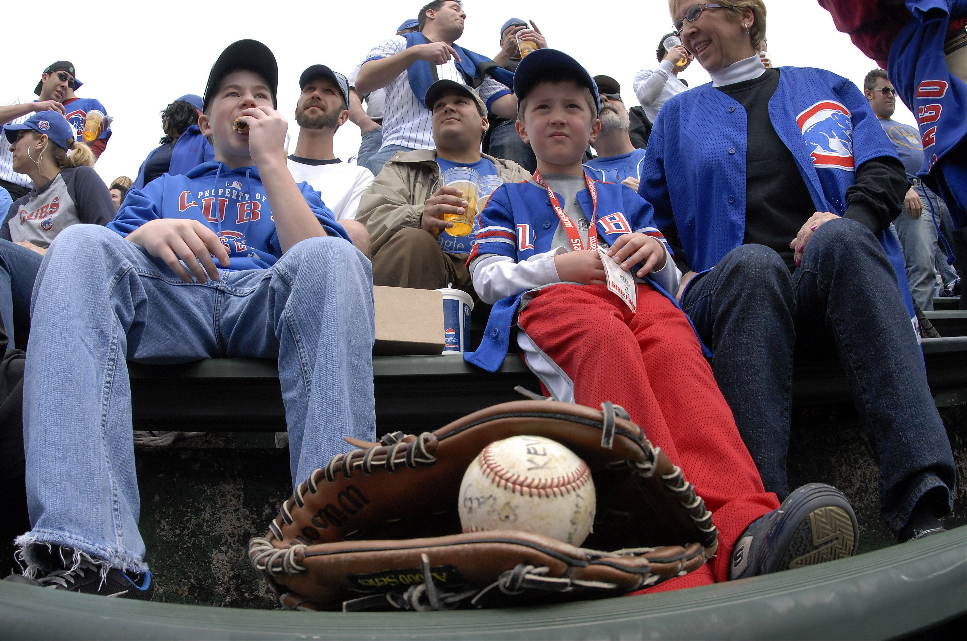 Getting a ball is one the Opening Day thrills experienced through the years by the Hruby family of Wheaton. In this 2010 photograph of the Wrigley Field bleachers, friend Kevin Riemer, 14, left, of Wheaton, cheers alongside Cal Hruby, 5, center, of Geneva, as Cal's grandmother Debra Hruby enjoys a warmer day than is expected for this year's opener.