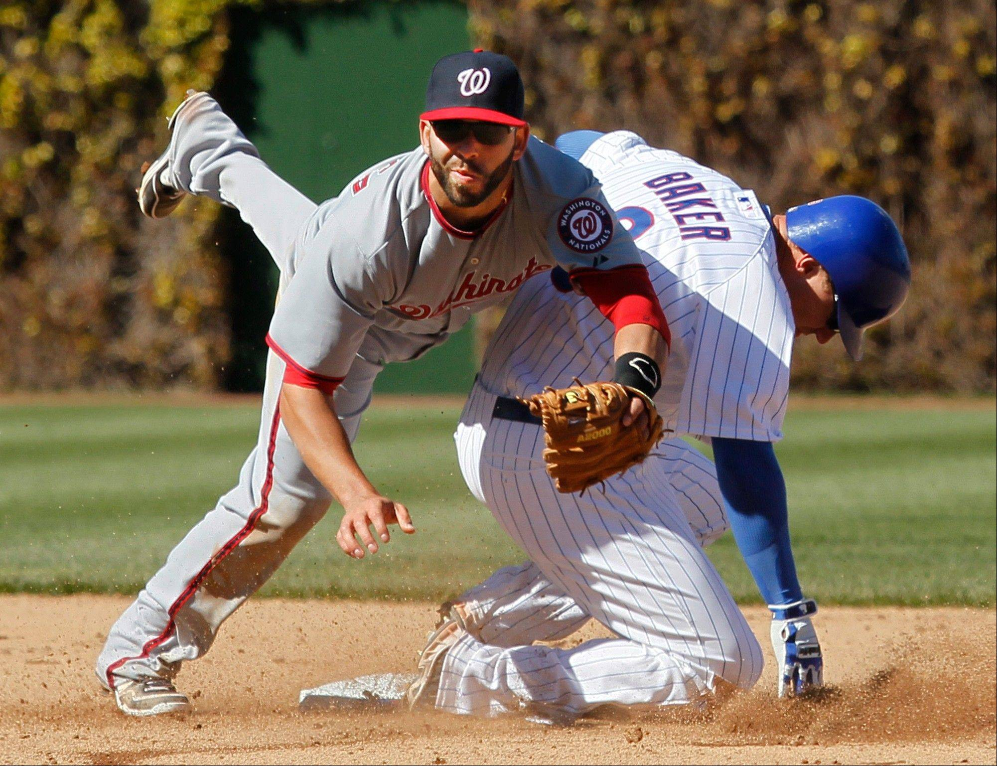 Washington Nationals second baseman Danny Espinosa, left, turns the double play forcing out Chicago Cubs' Jeff Baker at second and getting Marlon Byrd out at first during the seventh inning of an opening day baseball game, Thursday, April 5, 2012, in Chicago.