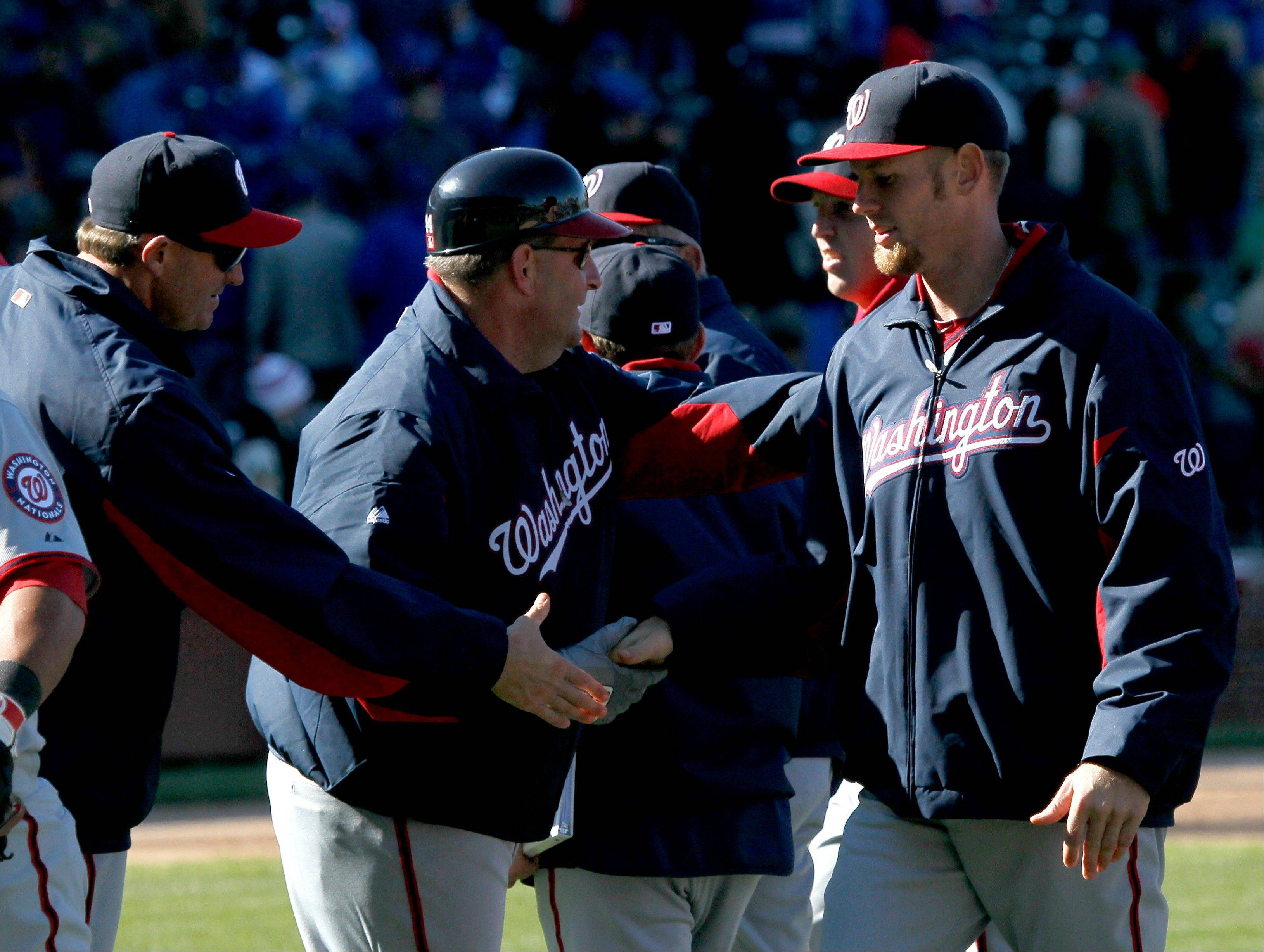 Washington Nationals starting pitcher Stephen Strasburg, right, celebrates with coaches after their 2-1 win in an opening day baseball game against the Chicago Cubs, Thursday, April 5, 2012, in Chicago.