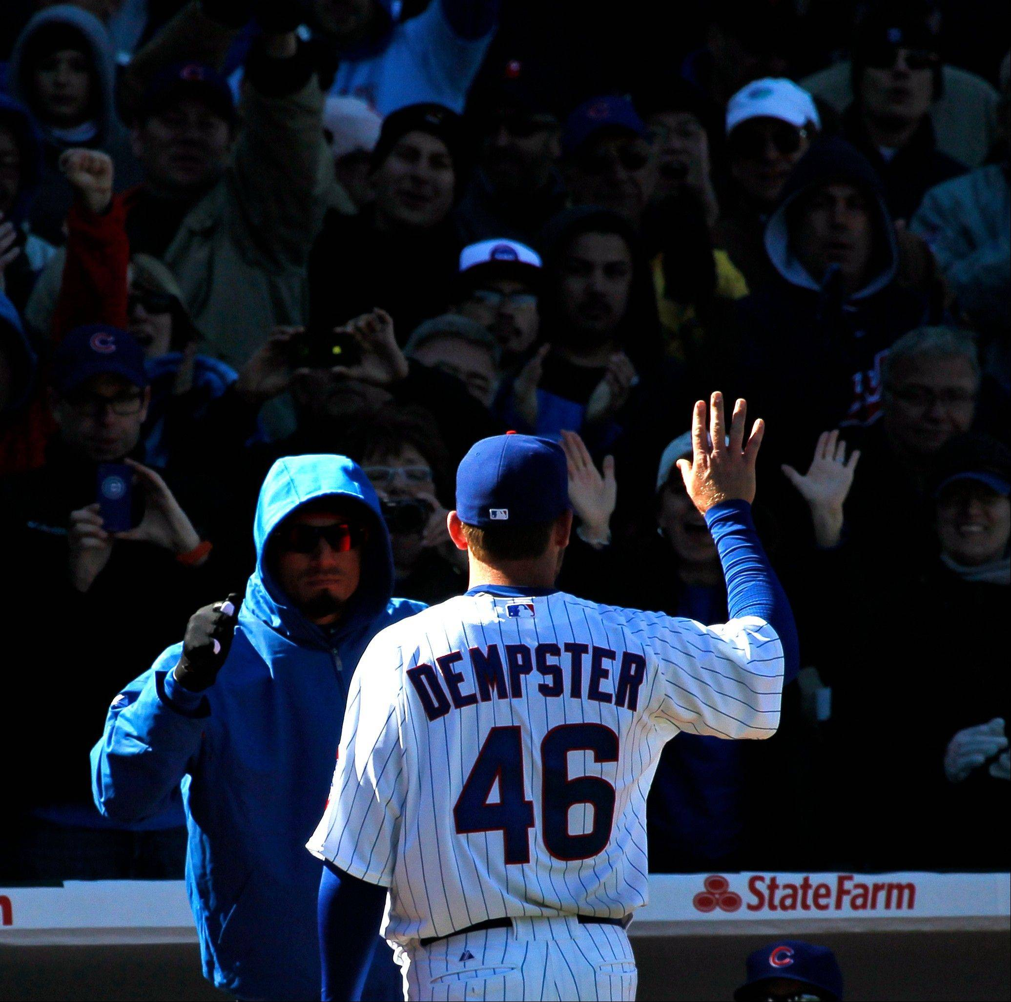 Chicago Cubs starting pitcher Ryan Dempster waves to the crowd as he leaves the game and walks towards a hooded Matt Garza in the dugout, during the eighth inning of an opening day baseball game against the Washington Nationals, Thursday, April 5, 2012, in Chicago. The Nationals won 2-1.