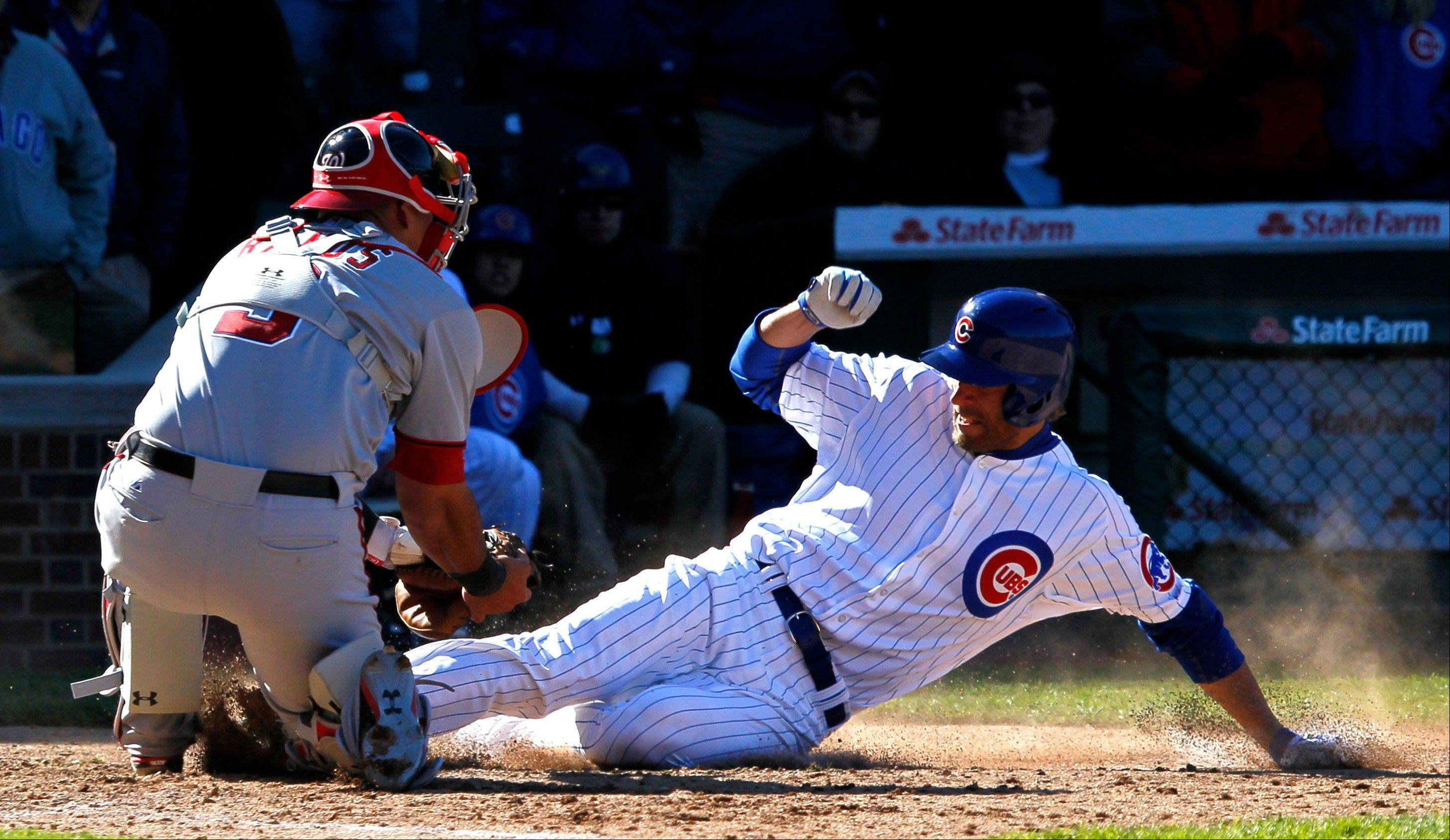 Washington Nationals catcher Wilson Ramos, left, tags out Chicago Cubs' Joe Mather, during the ninth inning of a baseball game, Thursday, April 5, 2012, in Chicago.