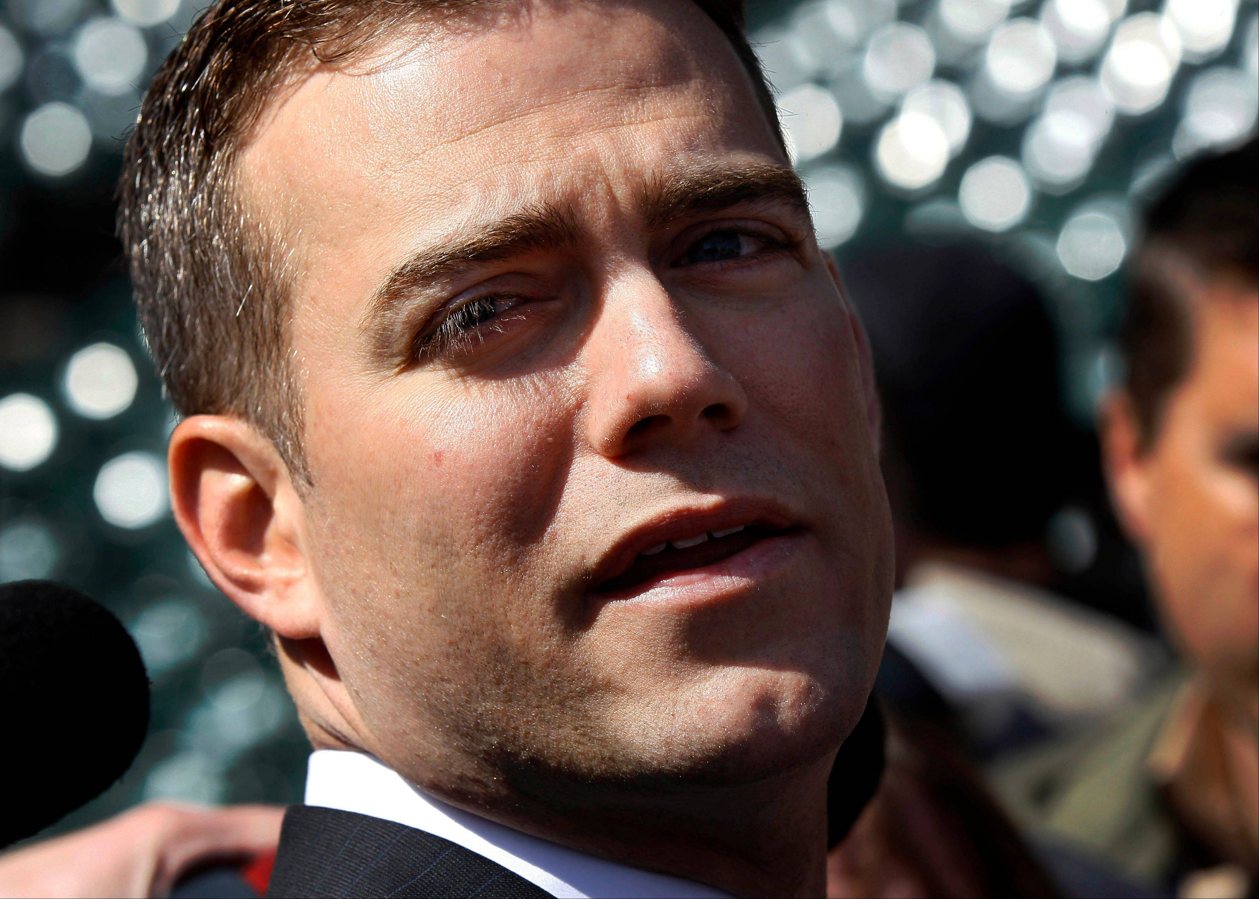 Chicago Cubs president Theo Epstein looks out over the field as he talks to reporters before an opening day baseball game against the Washington Nationals, Thursday, April 5, 2012, in Chicago.