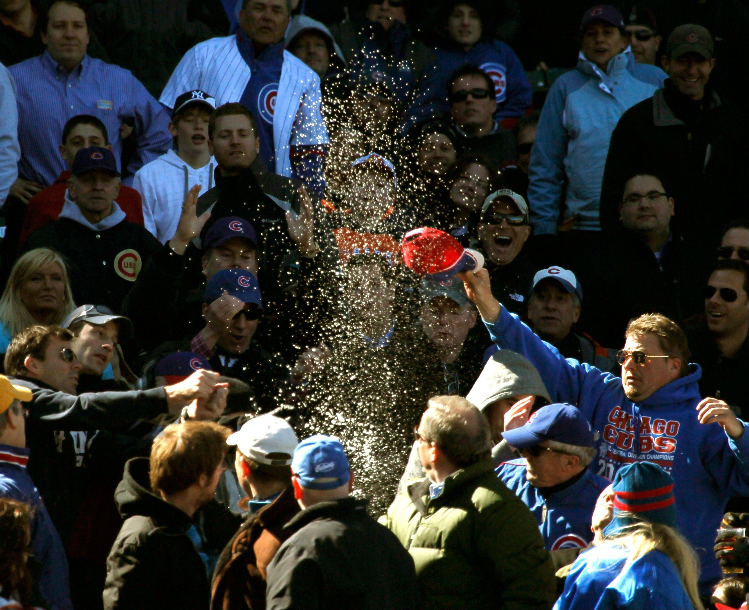 Baseball fans react after a foul ball hit by Chicago Cubs' Ian Stewart, off a pitch from Washington Nationals starting pitcher Stephen Strasburg, lands in a full beverage cup during the sixth inning of a baseball game, Thursday, April 5, 2012, in Chicago.