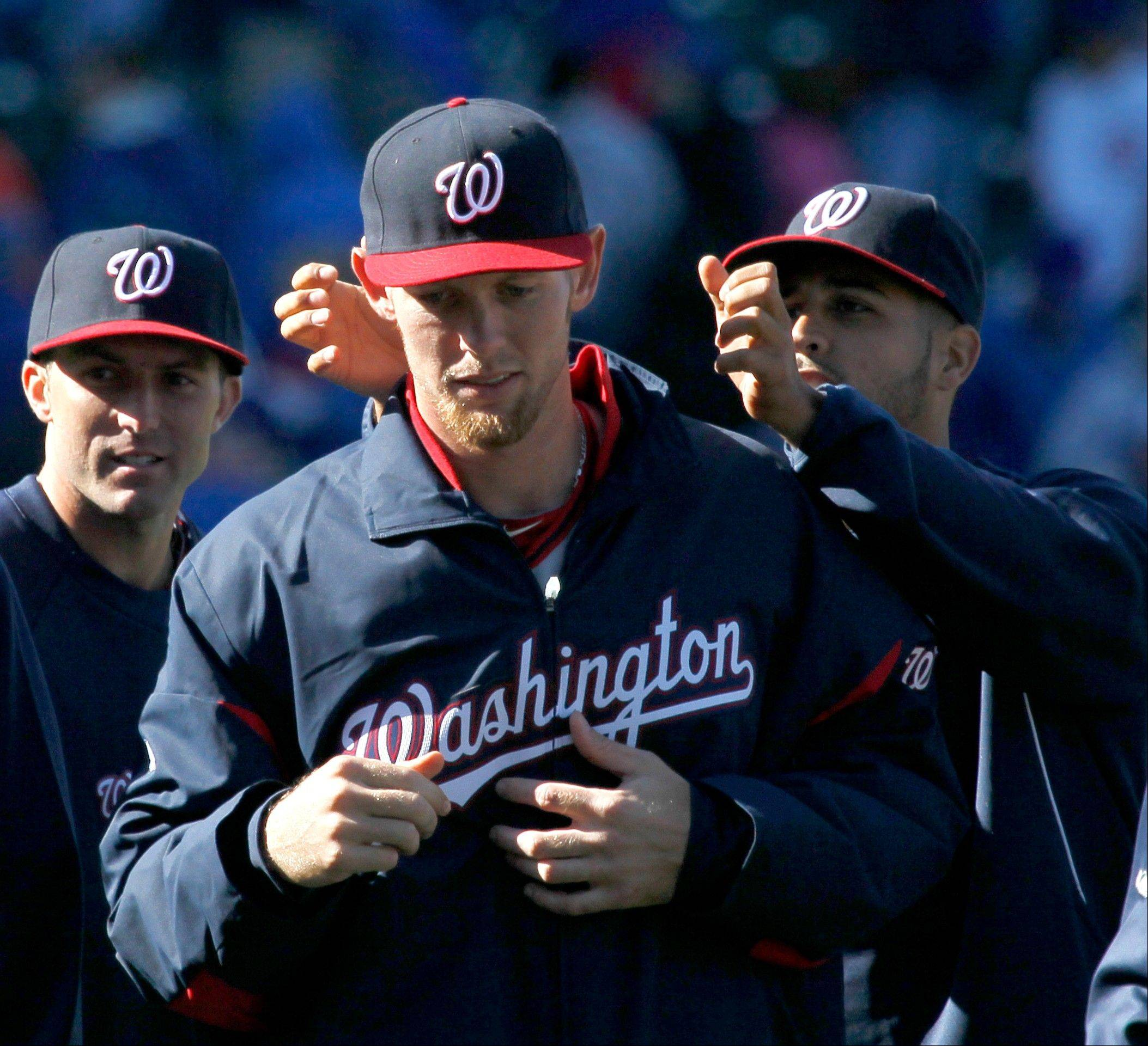 An unidentified teammate reaches behind Washington Nationals starting pitcher Stephen Strasburg and grabs his ears as they celebrate after their 2-1 win in an opening day baseball game against the Chicago Cubs, Thursday, April 5, 2012, in Chicago.