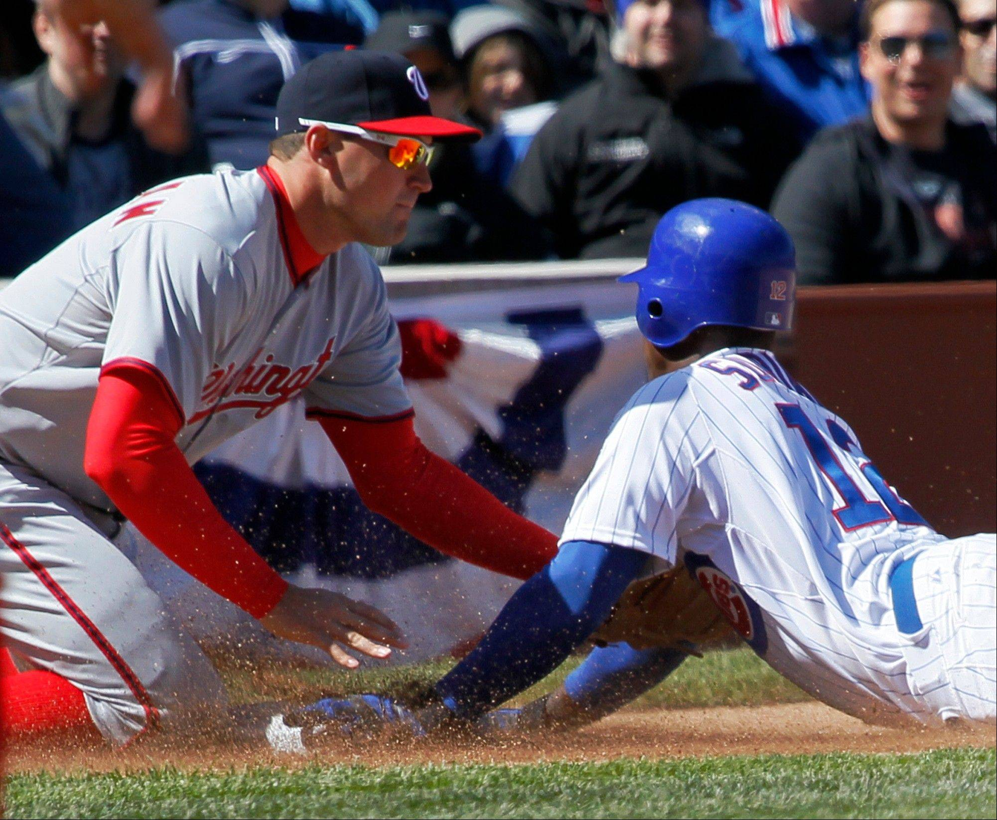 Chicago Cubs' Alfonso Soriano, right, is caught stealing third as Washington Nationals third baseman Ryan Zimmerman applies the tag from the throw of catcher Wilson Ramos in the fourth inning of an opening day baseball game, Thursday, April 5, 2012, in Chicago.