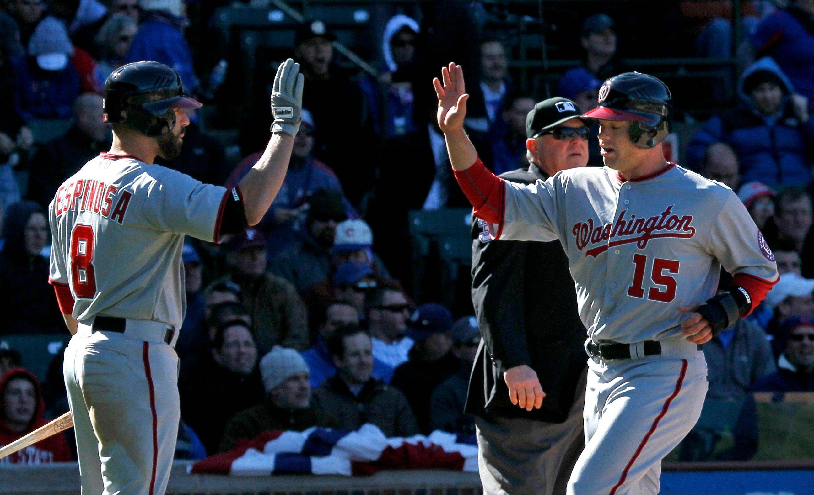 Washington Nationals' Danny Espinosa (8) greets pinch runner Brett Carroll, after Carroll scored on a hit by Ian Desmond, during the ninth inning of an opening day baseball game against the Chicago Cubs, Thursday, April 5, 2012, in Chicago. The Nationals won 2-1.