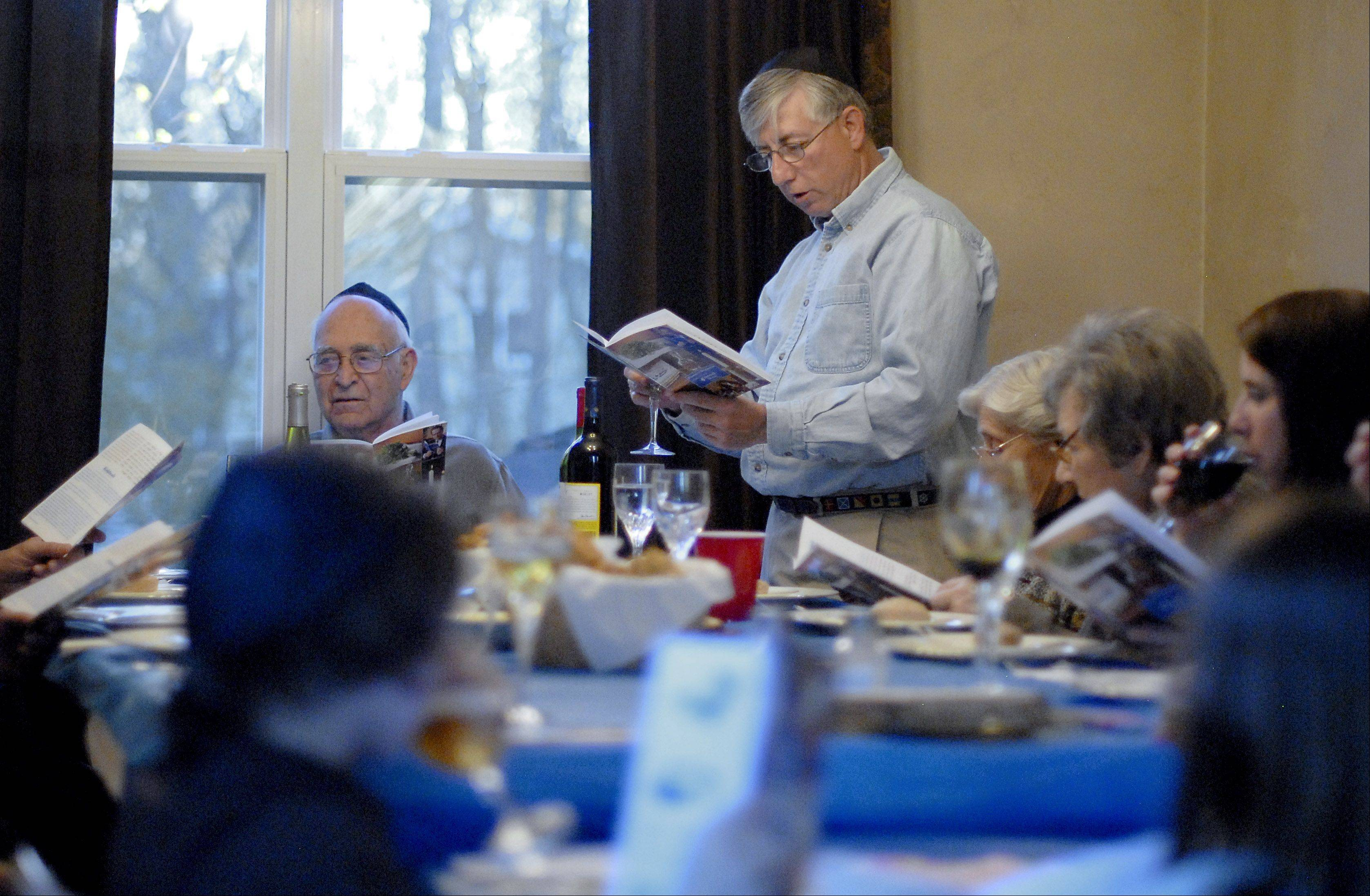 Chuck Fogel of Chicago reads from the Passover Haggada at his sister Barb Anderson's home in St. Charles on Friday. Anderson has been hosting the Seder for her family for the past 10 years.