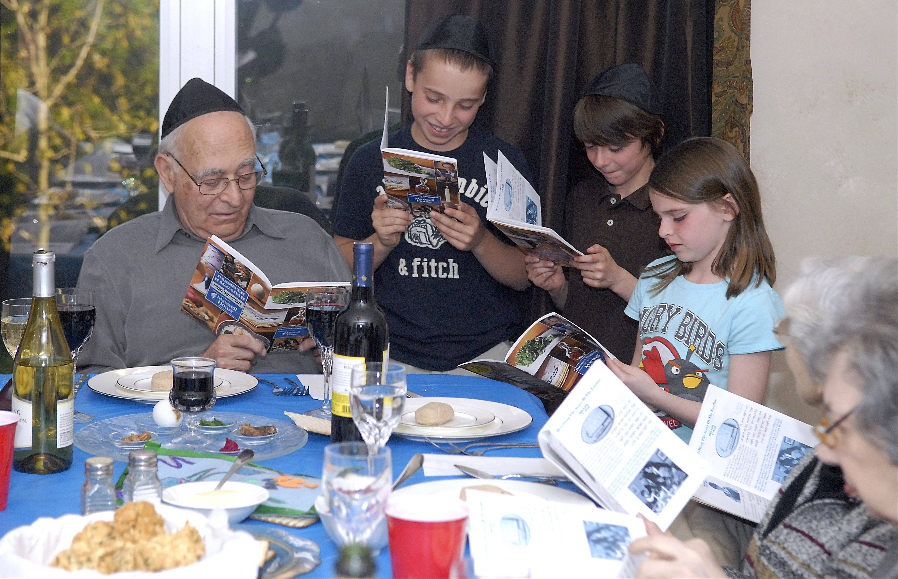 Archie Fogel of Mt. Prospect listens to his grandchildren Ben Anderson, 11, Jacob Fogel, 11, and Gena Fogel, 9, read from the Passover Haggada prayer book at their family's Passover Seder on Friday. Ben's mother, Barb, hosts the family Passover Seder in their St. Charles home. Siblings Jacob and Gena are from Cary. Barb and her husband, Jeff, have been hosting the Seder for the past 10 years, which was hosted by her mother, Joyce, prior.