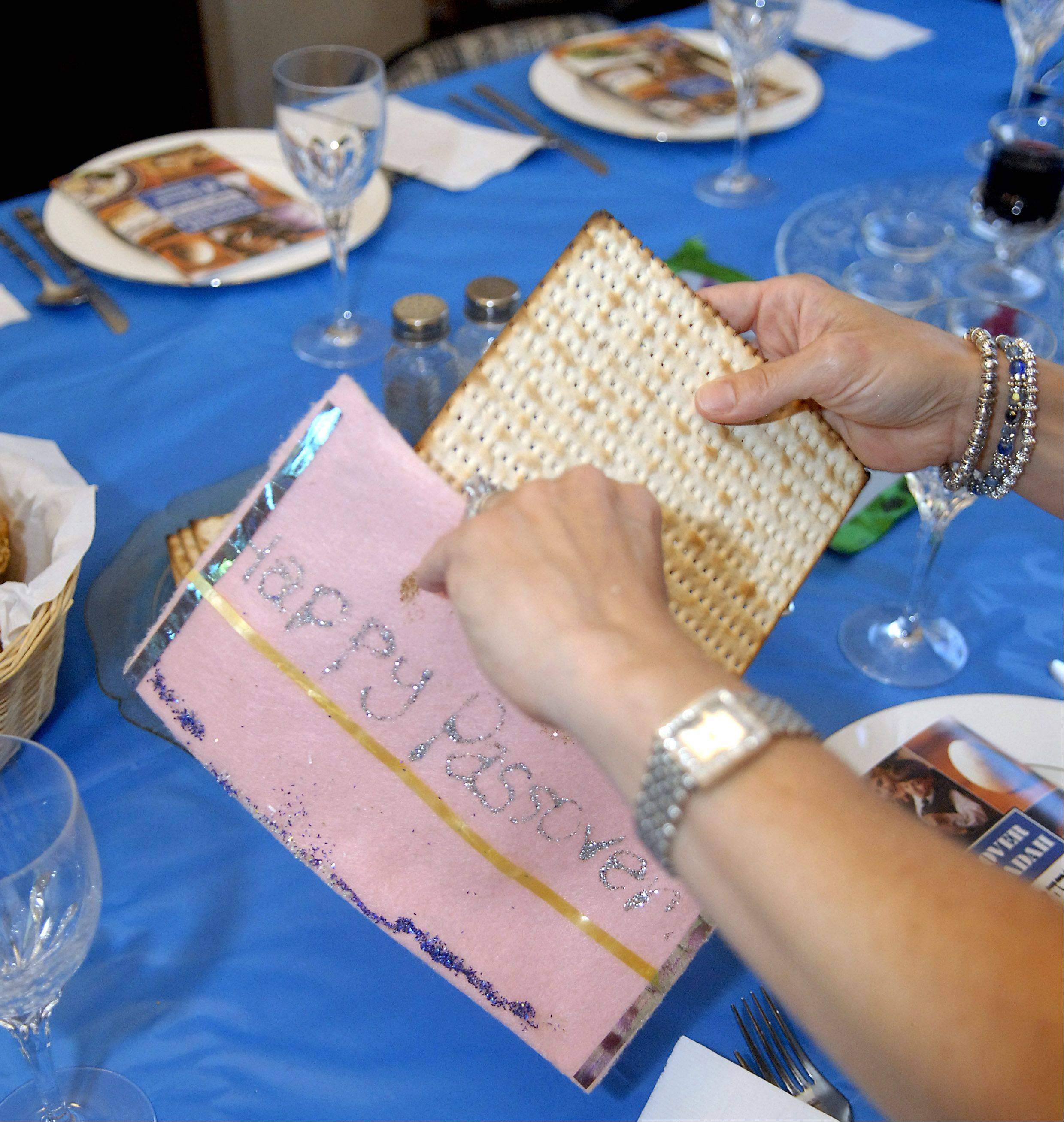 Barb Anderson hides a matzo cracker in a felt pouch made by her daughter, Sarah, 13.