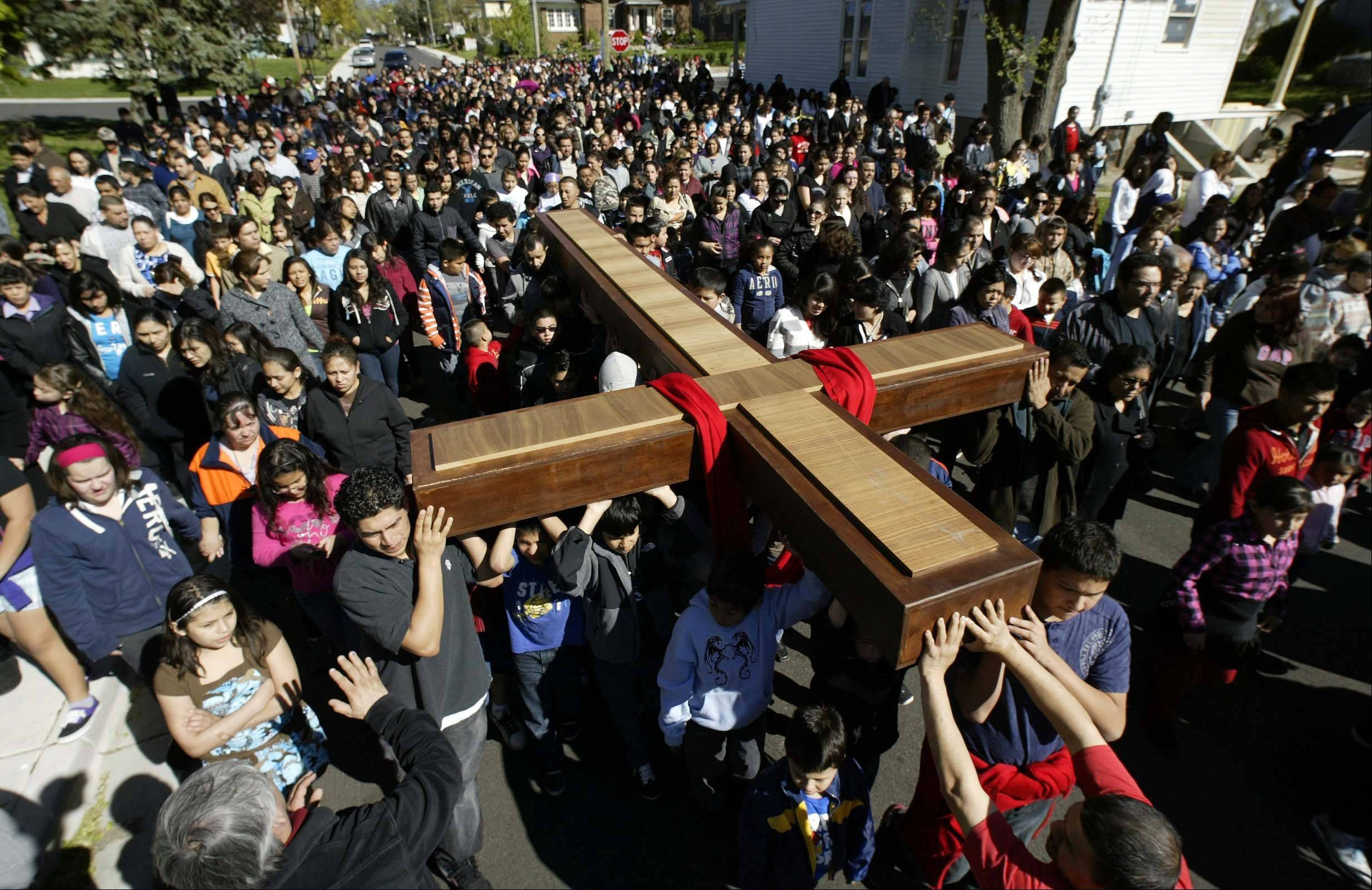 Hundreds crowded the streets during St. Joseph Catholic Church's annual passion march along Division Street in Elgin. Parishioners took turns carrying the cross as the large crowd made their way through the neighborhood.