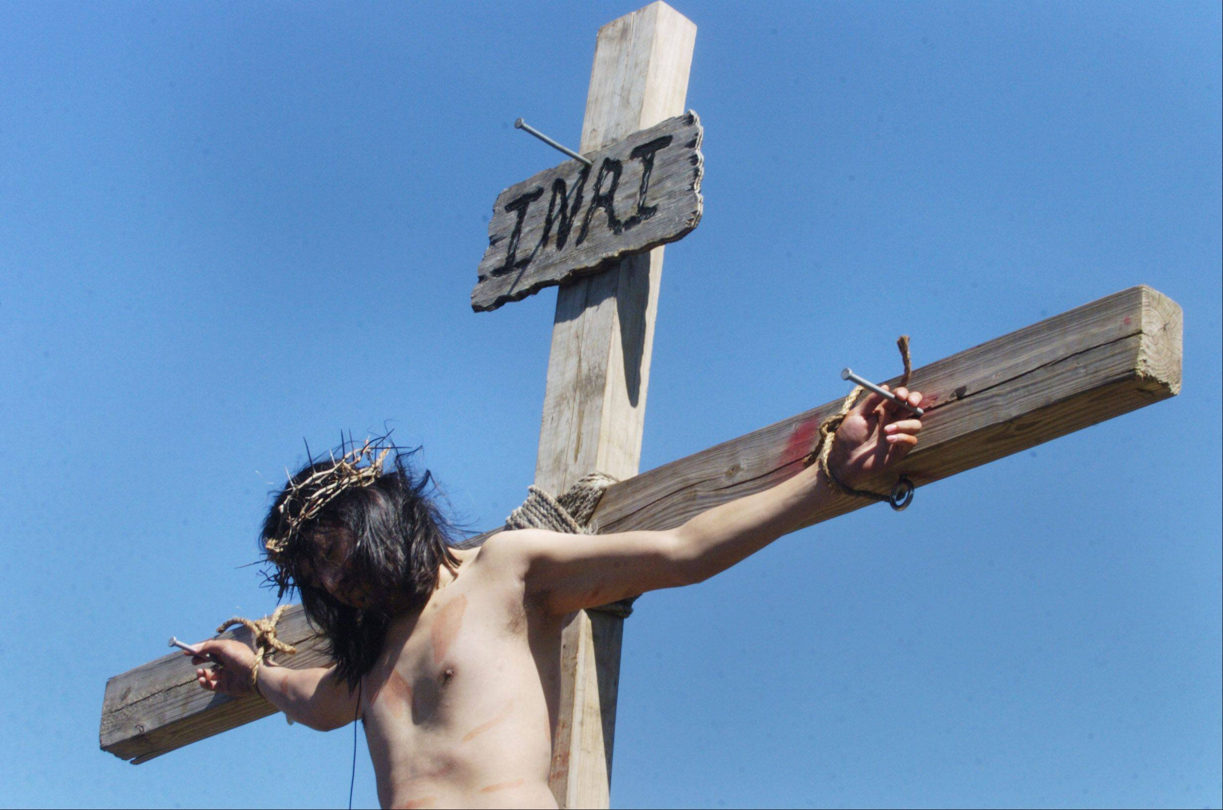 Jesus, played by Martin Carrera, hangs on the cross during the live Way of the Cross procession at Mission San Juan Diego in Arlington Heights on Good Friday.