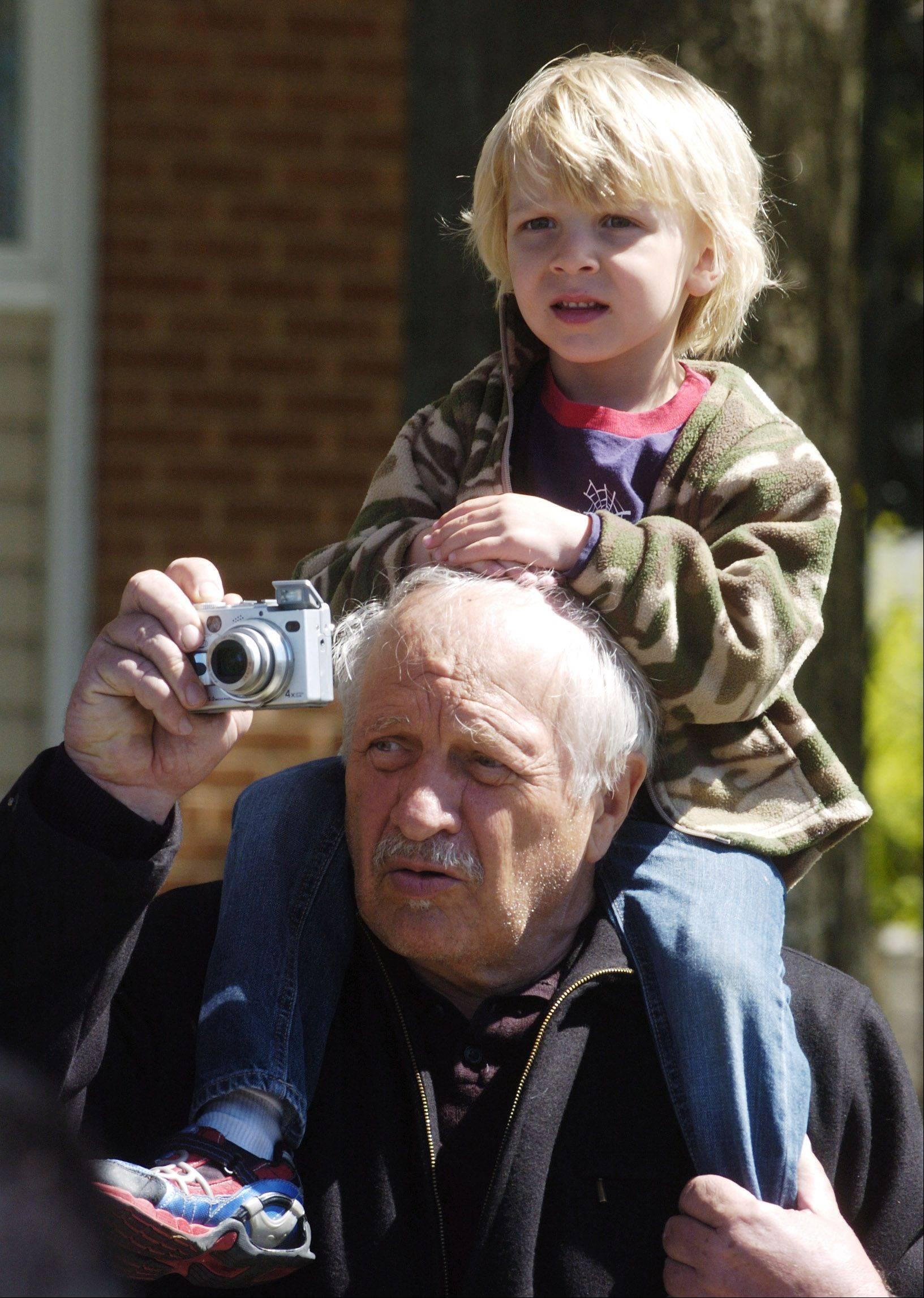 Stefan Smolak, 4, of Palatine, rests on the shoulders of his grandfather George Smolak of Arlington Heights as George takes a picture during the live Way of the Cross procession between St. Thomas of Villanova in Palatine and Mission San Juan Diego in Arlington Heights on Good Friday.
