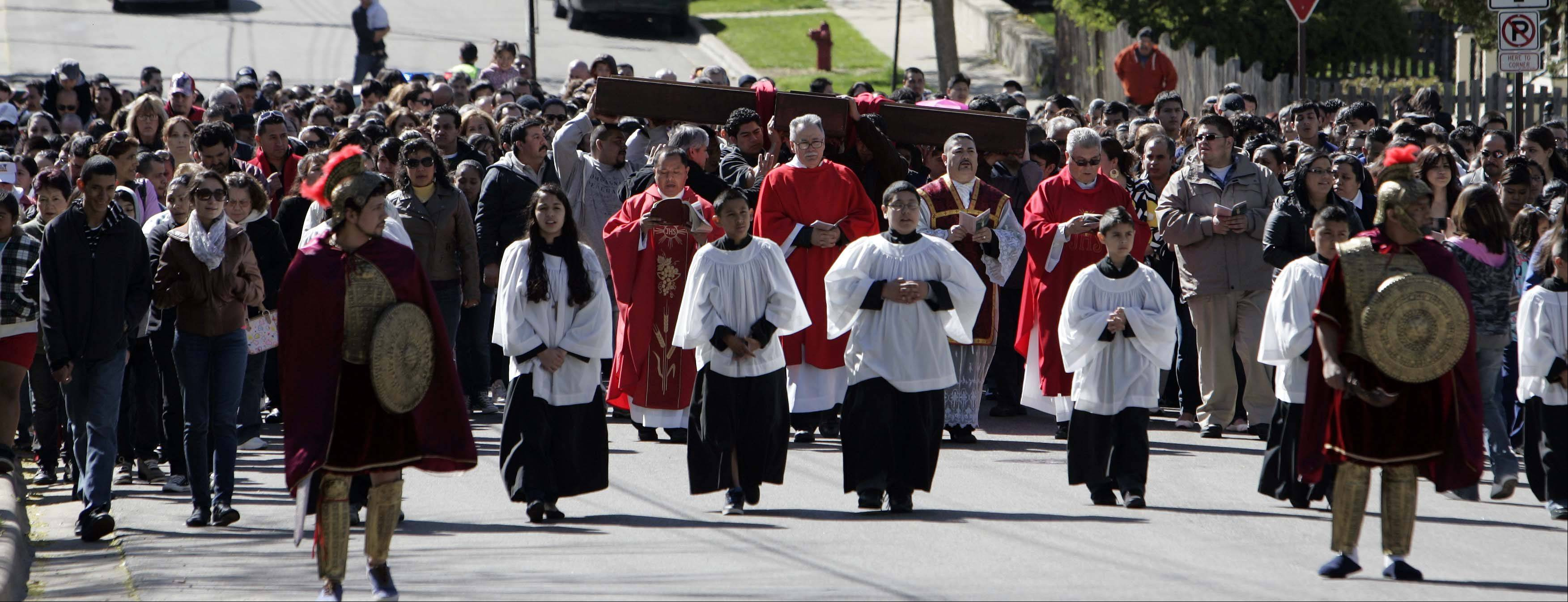 Hundreds crowded the streets during St. Joseph's Annual passion march along Division Street in Elgin.
