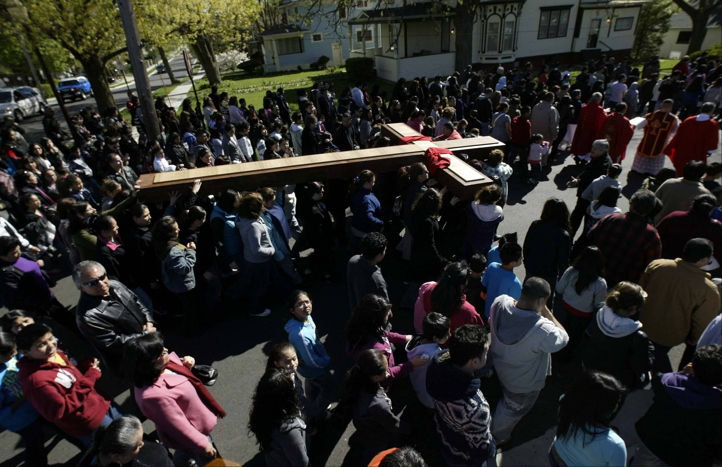 The cross travels back to St. Joseph Church during the Annual passion march in Elgin.