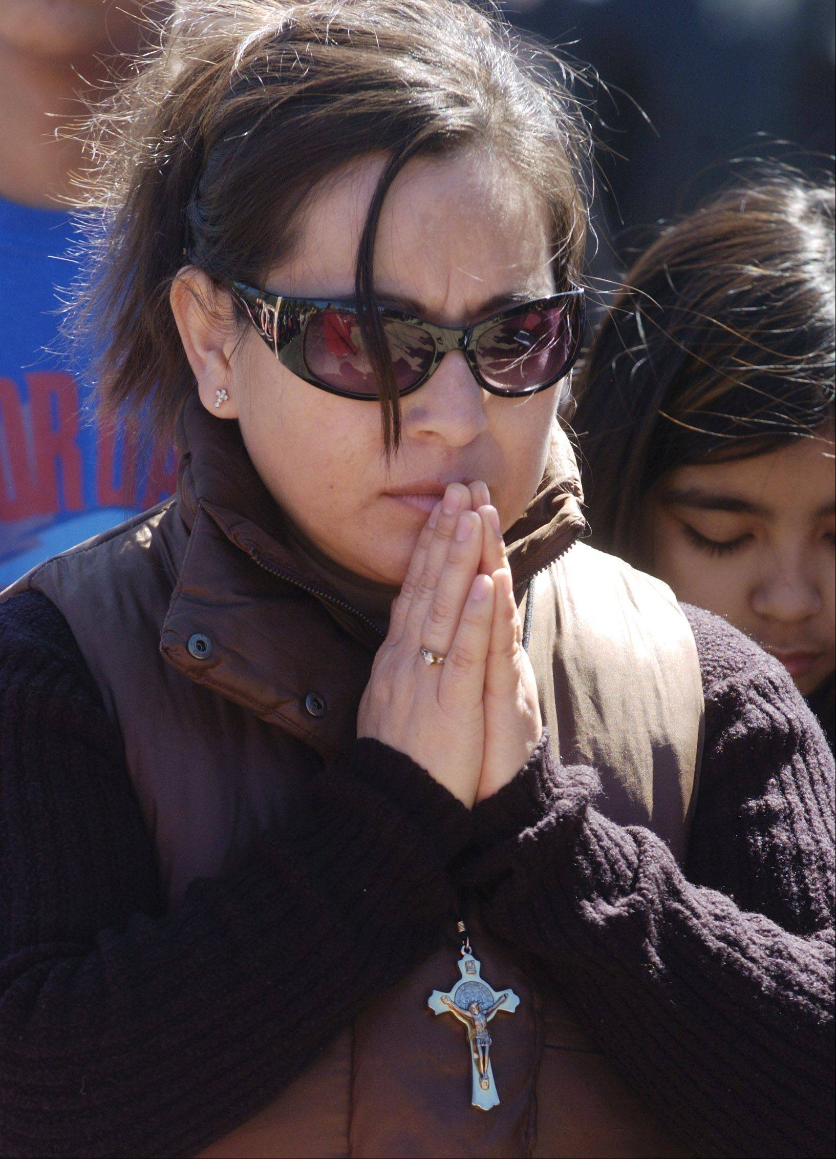 Carmen Mendez of Palatine prays during the live Way of the Cross procession between St. Thomas of Villanova in Palatine and Mission San Juan Diego in Arlington Heights on Good Friday.