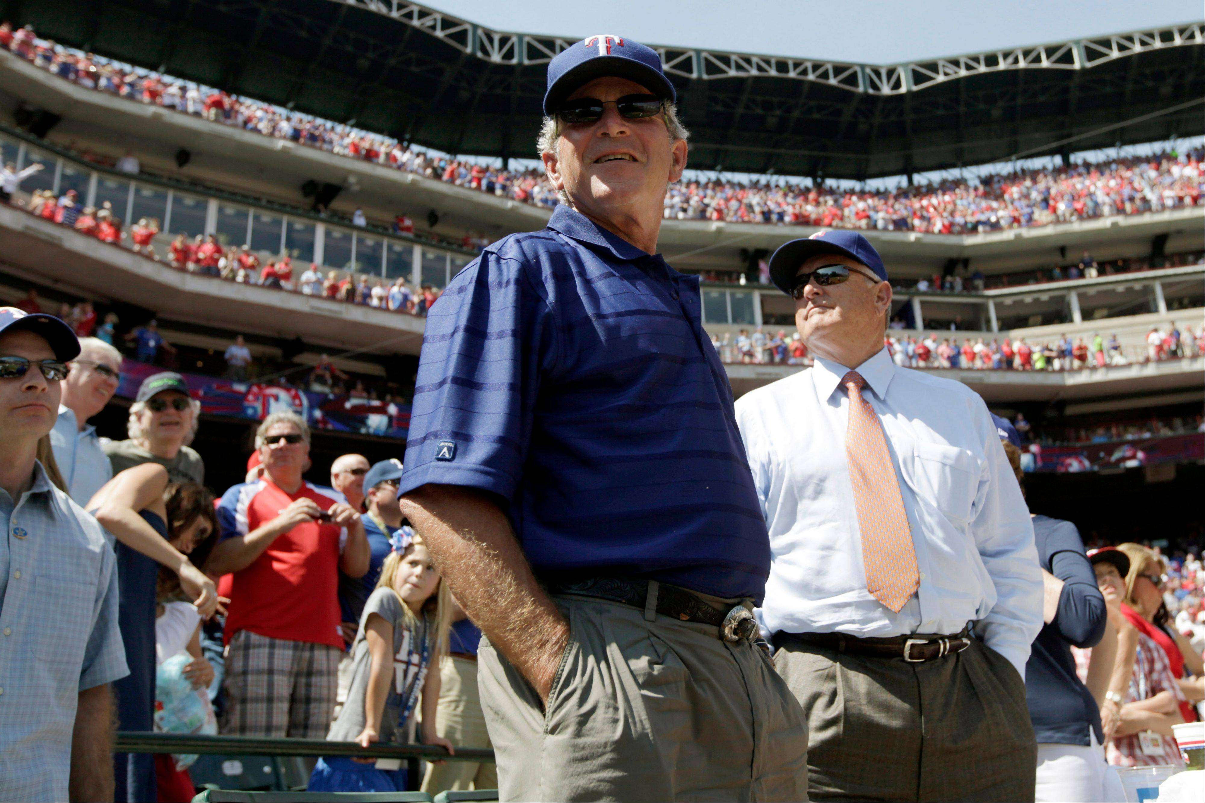 Former President George W. Bush and Texas Rangers President and CEO Nolan Ryan stand during the seventh inning stretch against the Chicago White Sox on Friday in Arlington, Texas.