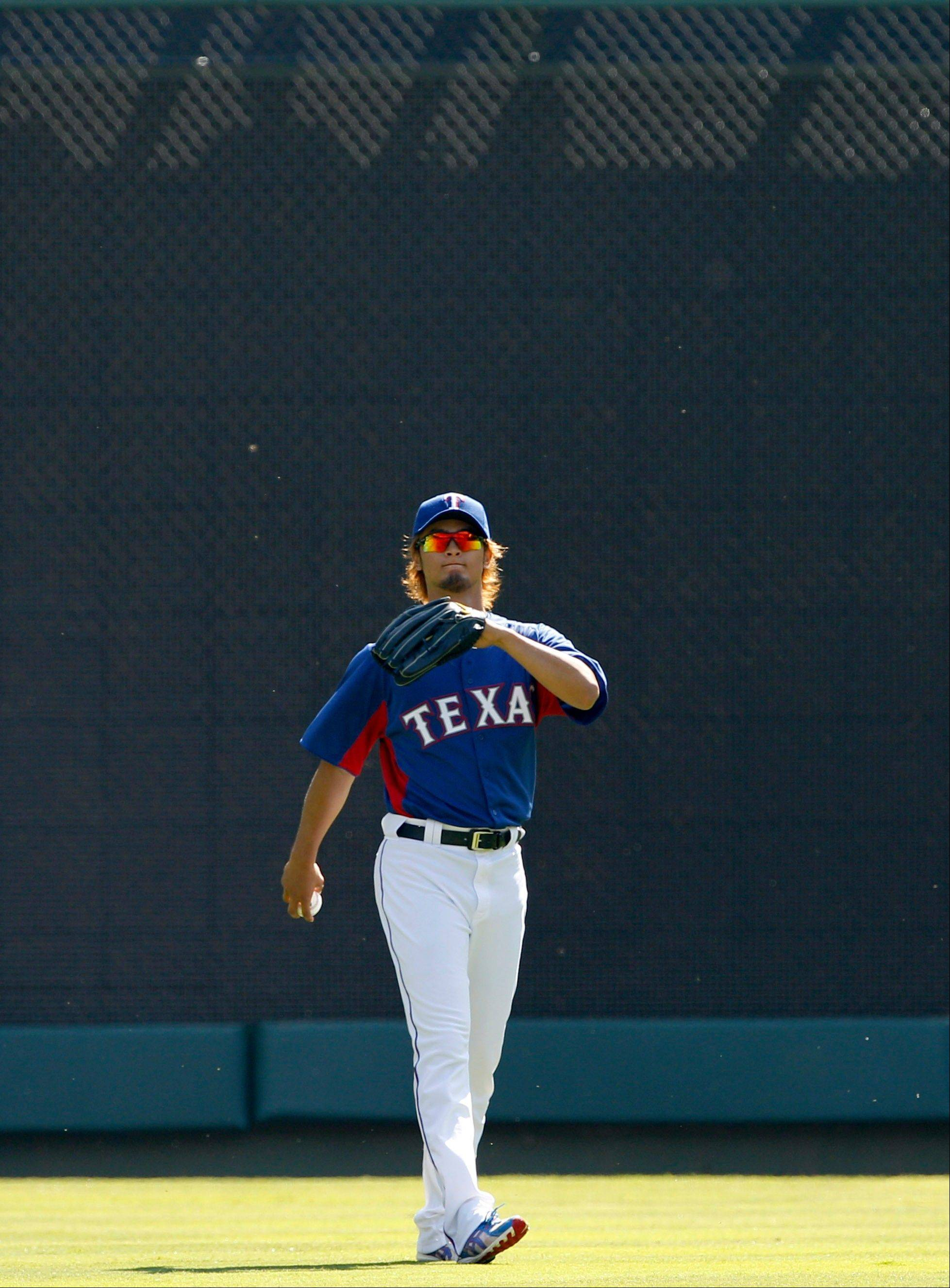 Texas Rangers starting pitcher Yu Darvish of Japan, warms up in the outfield before a baseball game against the Chicago White Sox Friday, April 6, 2012 in Arlington, Texas.