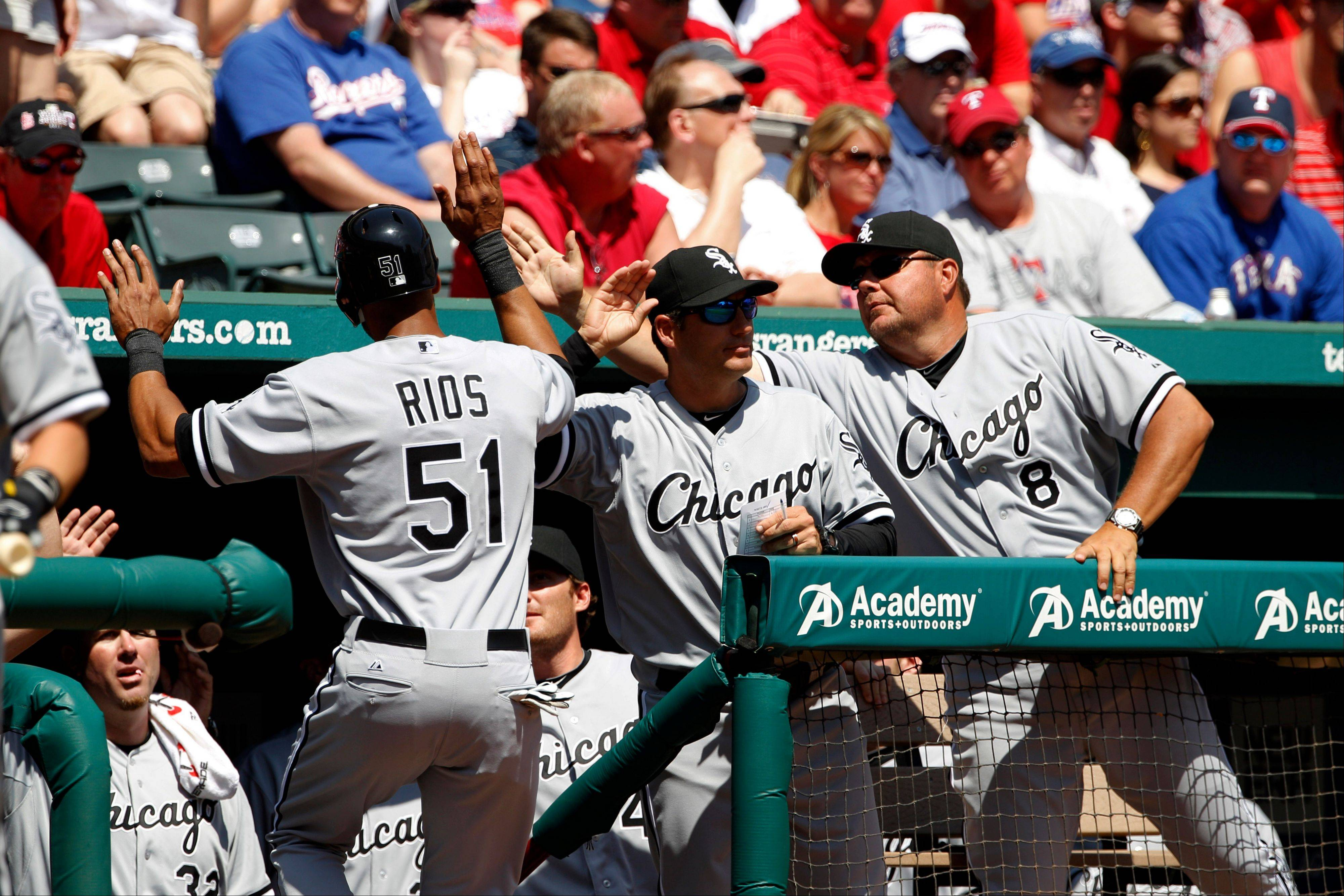 Chicago White Sox's Alex Rios (51) celebrates in the dugout after scoring on a single by Alexei Ramirez against the Texas Rangers during the sixth inning of a baseball game, Friday, April 6, 2012, in Arlington, Texas.