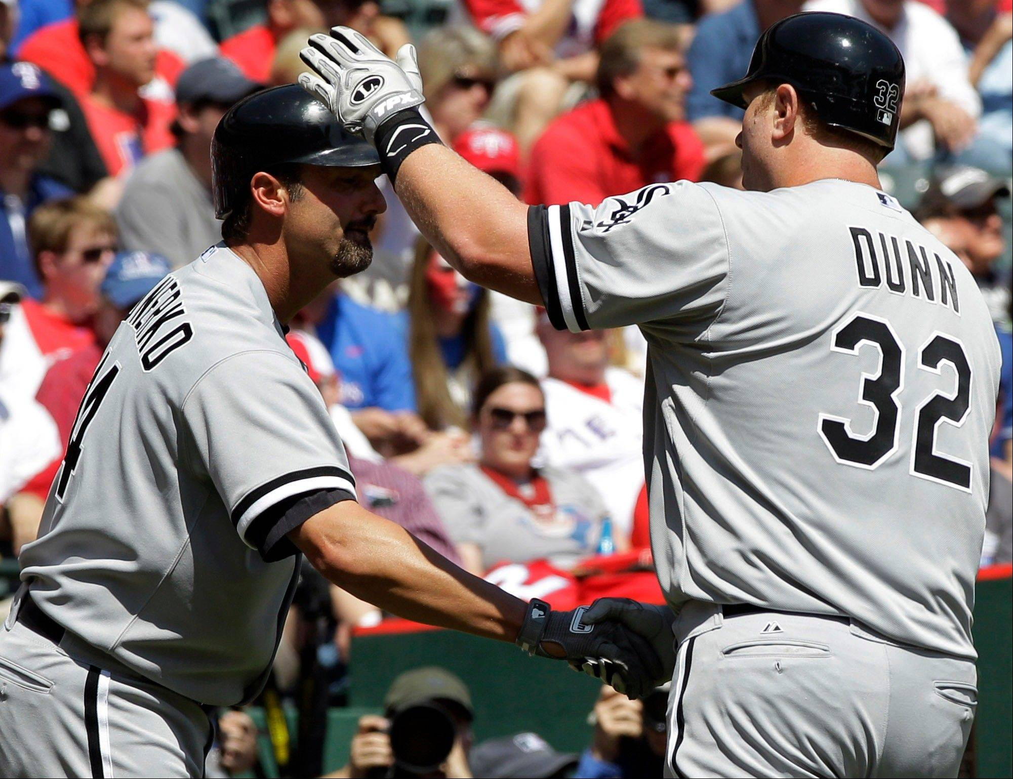 Chicago White Sox's Paul Konerko, left, congratulates Adam Dunn (32) after Dunn hit a solo home run against the Texas Rangers during the sixth inning of a baseball game, Friday, April 6, 2012, in Arlington, Texas.