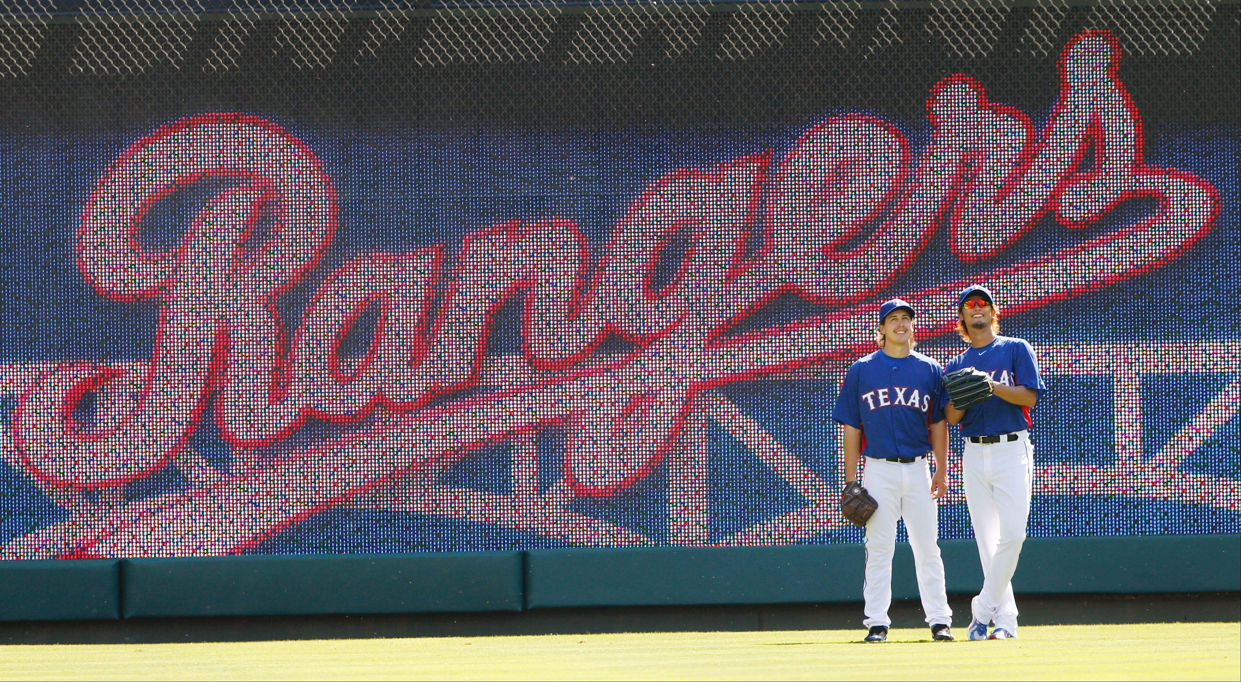 Texas Rangers starting pitcher Derek Holland, left, and and starting pitcher Yu Darvish of Japan, warm up in the outfield before a baseball game against the Chicago White Sox Friday, April 6, 2012 in Arlington, Texas.