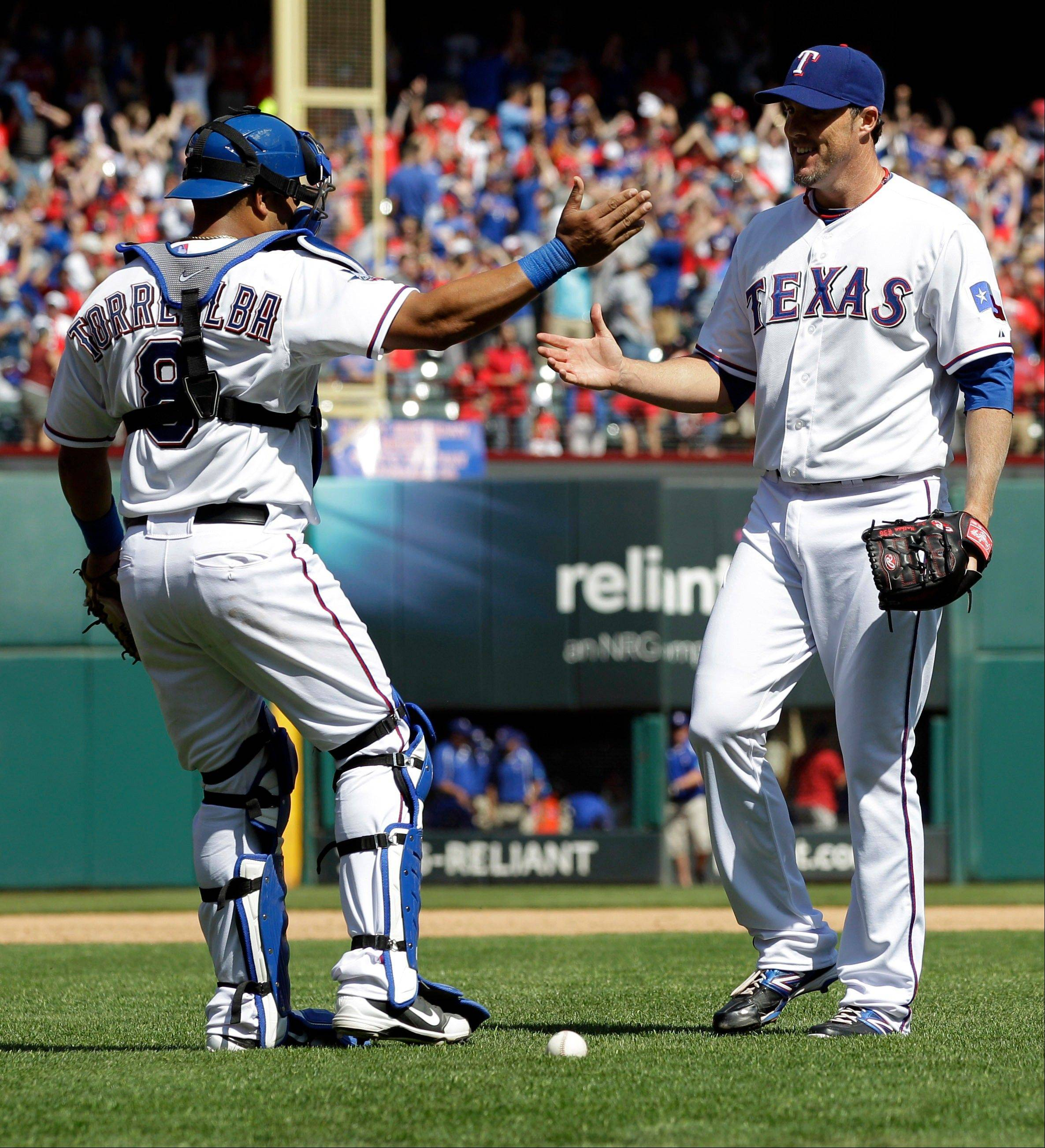 Texas Rangers catcher Yorvit Torrealba (8) and closer Joe Nathan (36) react after defeating the Chicago White Sox 3-2 in a baseball game, Friday, April 6, 2012, in Arlington, Texas.