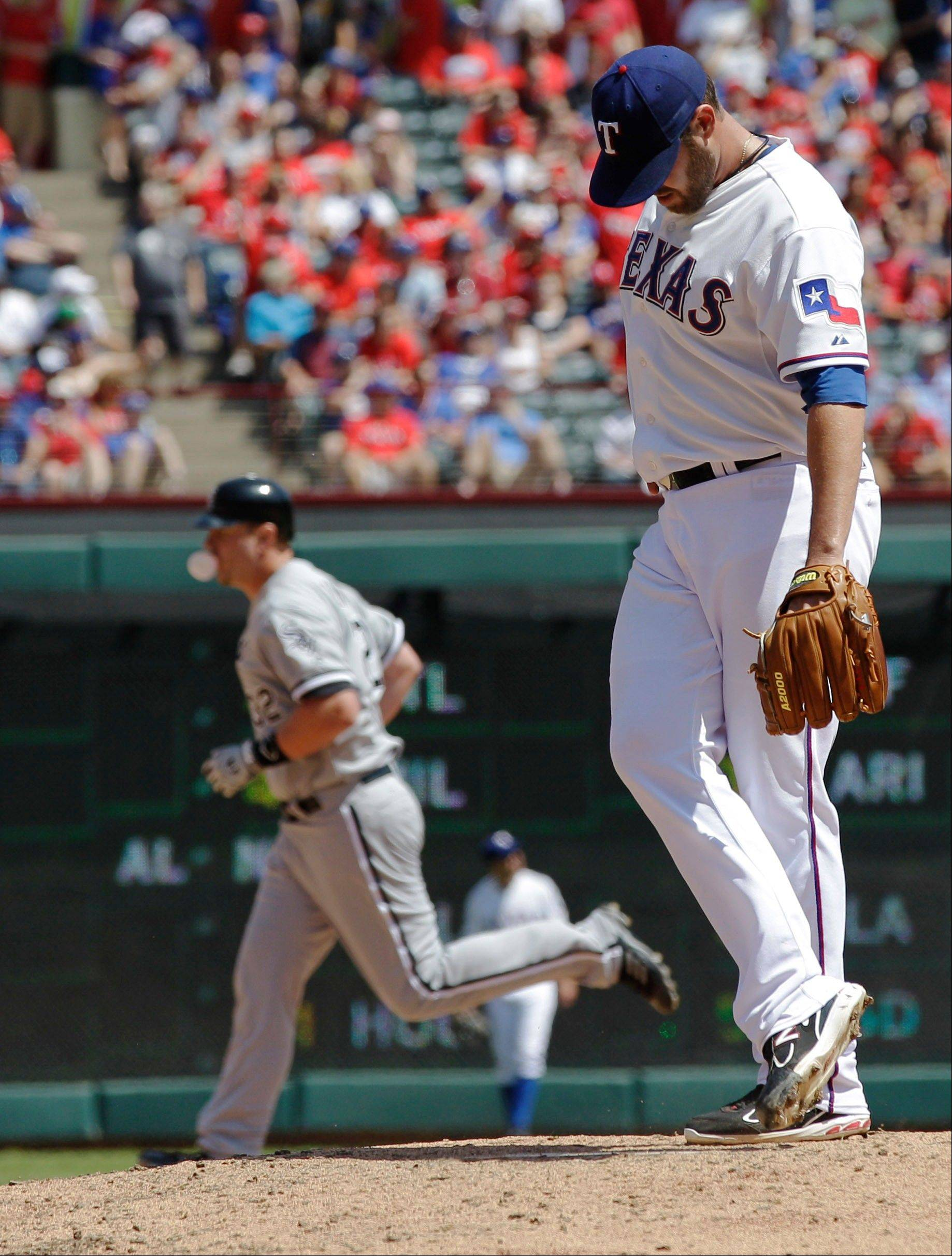 Texas Rangers starting pitcher Colby Lewis clears the mound as Chicago White Sox's Adam Dunn rounds the bases after hitting a solo home run during the sixth inning of a baseball game, Friday, April 6, 2012, in Arlington, Texas.