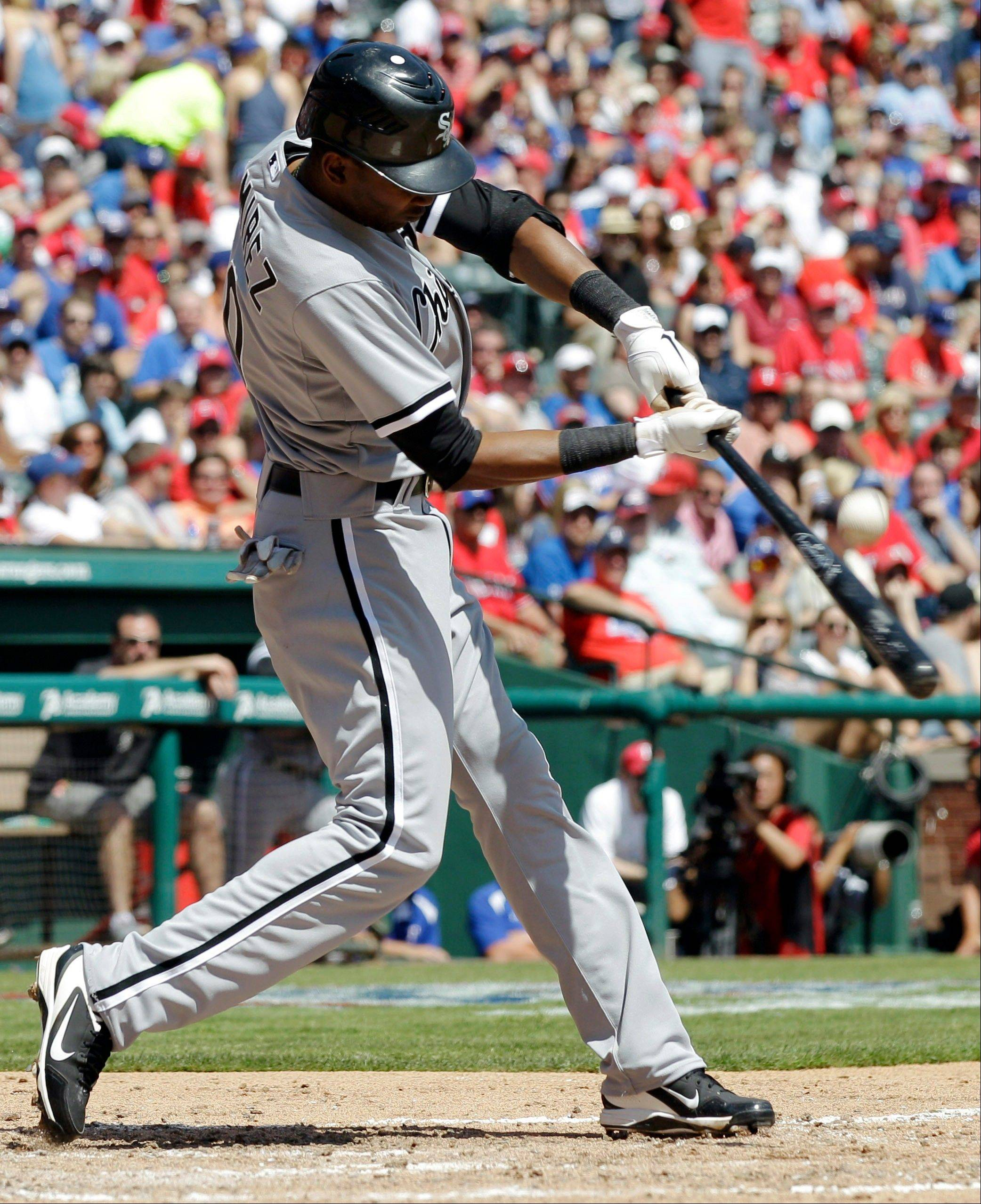 Chicago White Sox's Alexei Ramirez hits an RBI single against the Texas Rangers during the sixth inning of a baseball game, Friday, April 6, 2012, in Arlington, Texas.