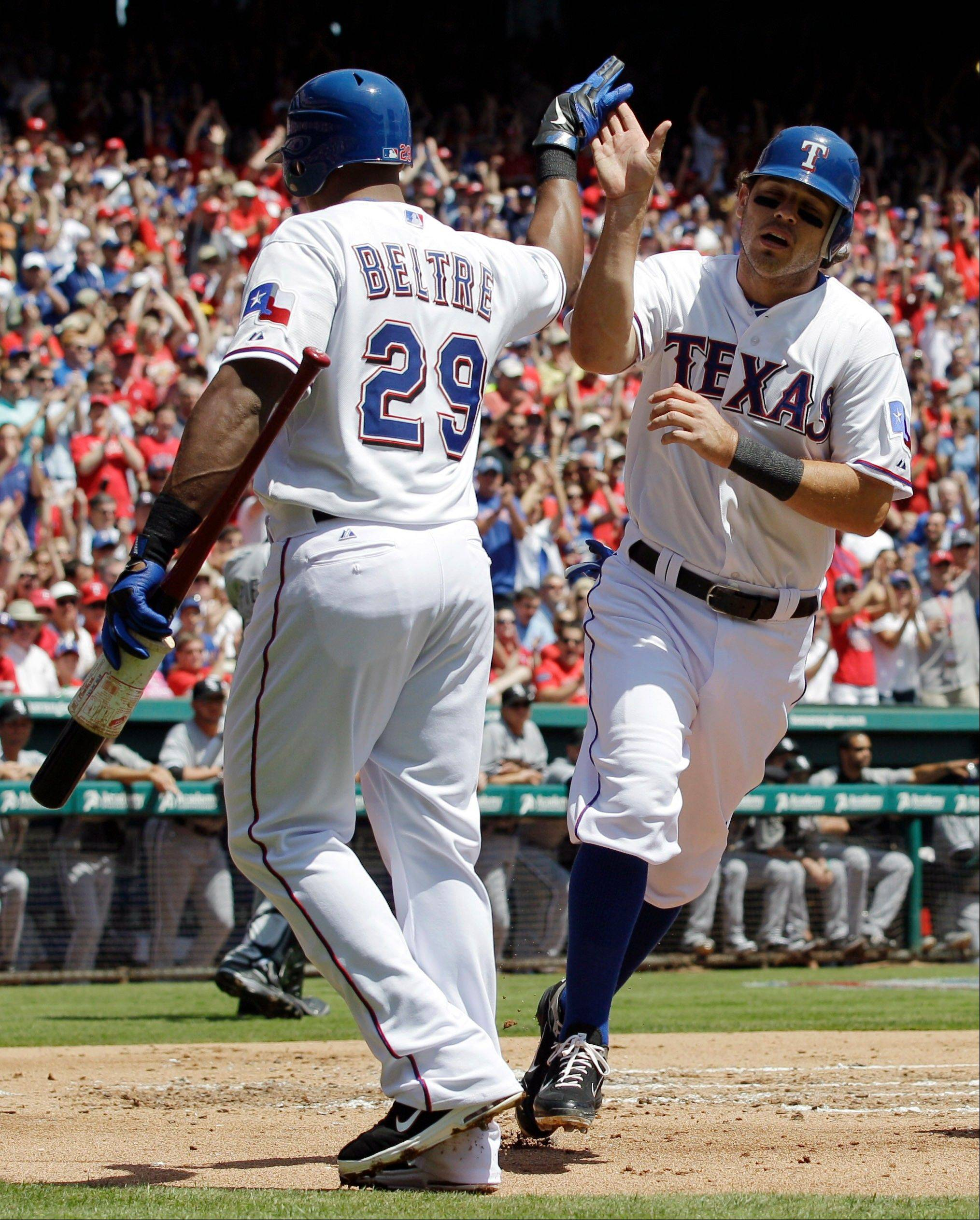 Texas Rangers' Adrian Beltre (29) congratulates Ian Kinsler who scored on a sacrifice fly by Josh Hamilton against the Chicago White Sox during the first inning of a baseball game Friday, April 6, 2012 in Arlington, Texas.
