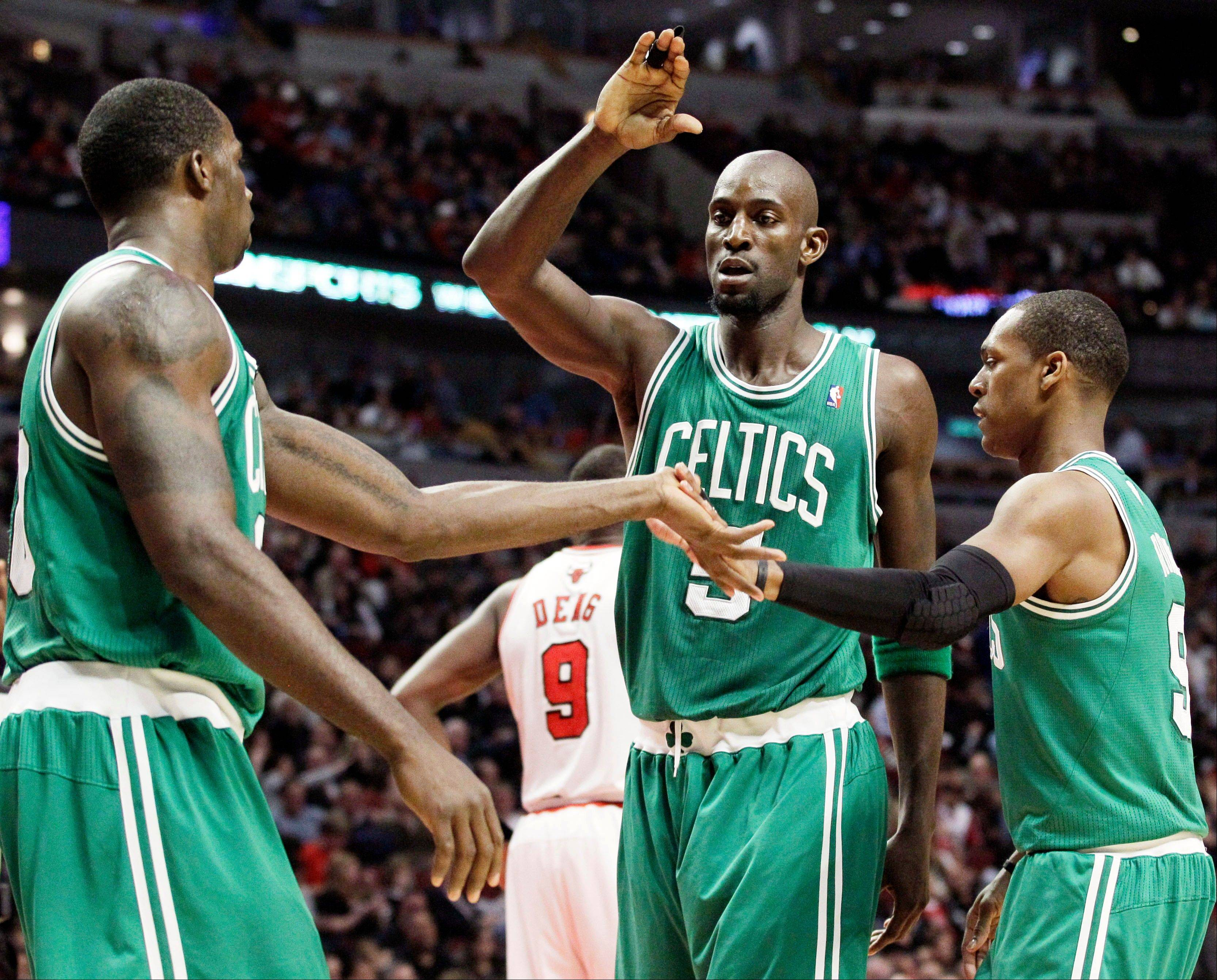 Boston Celtics forward Brandon Bass, left, celebrates with forward Kevin Garnett (5) and guard Rajon Rondo (9) after scoring a basket during the first half of an NBA basketball game against the Chicago Bulls in Chicago, Thursday, April 5, 2012.