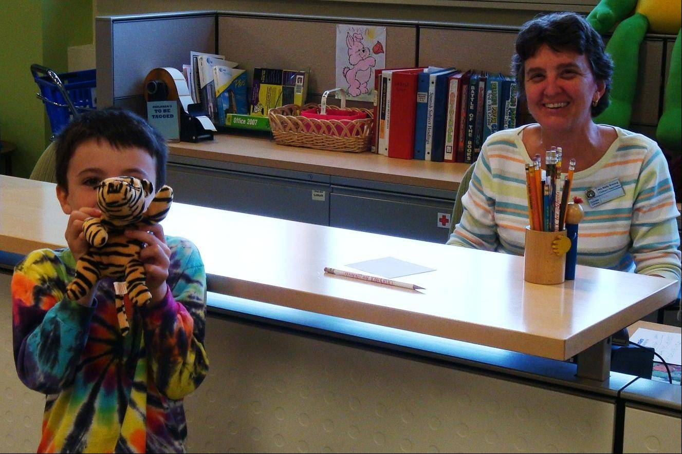 "Devan McTague checks in his beloved tiger,""Tiggy,"" with children's librarian Kathy Stensing at the Dundee Library for the ""Critter Campout"" on April 9-14."