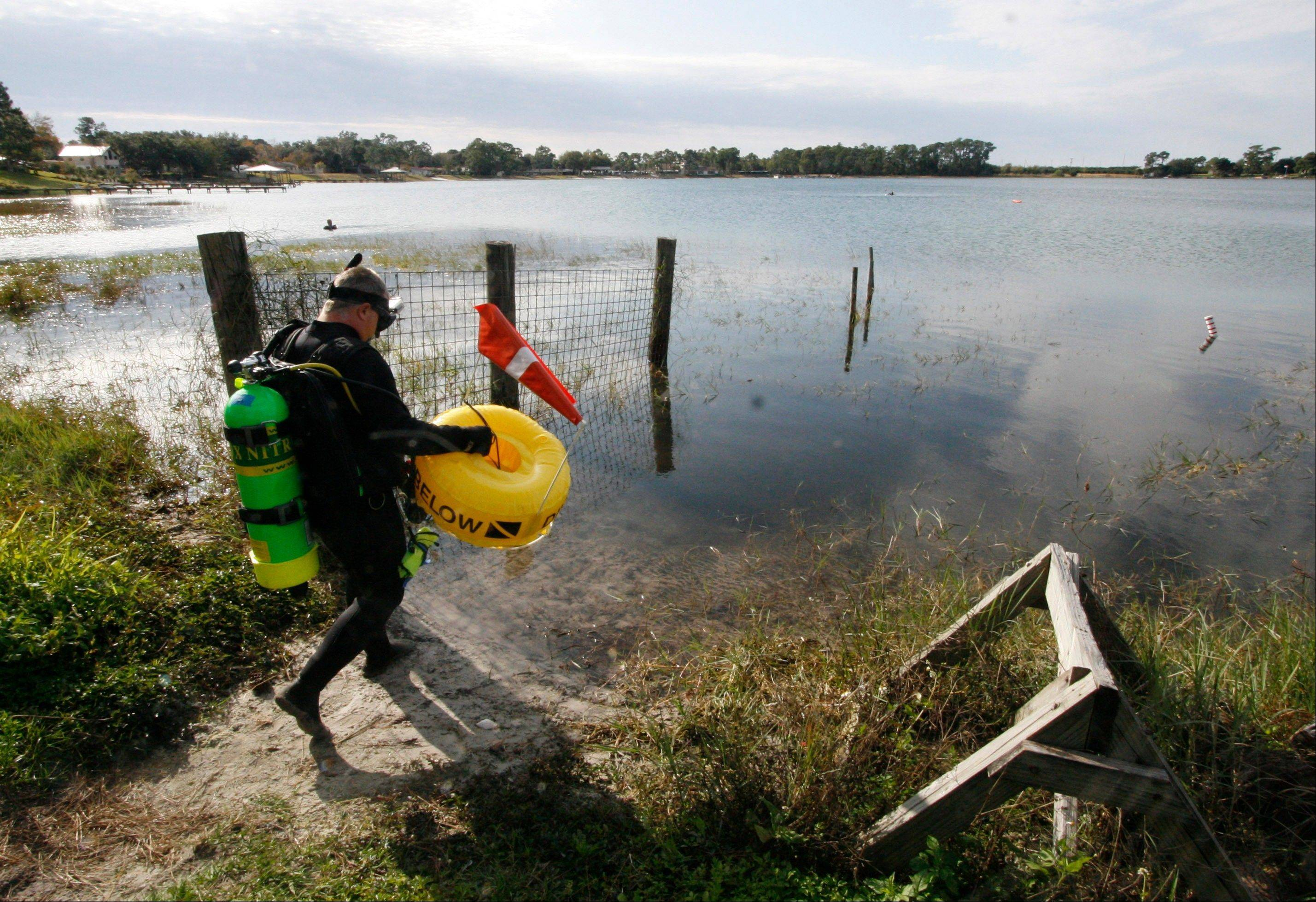 "Kenny Jenkins carries a float with a ""Diver Down"" flag as he prepares to place a geocache in Lake Denton in Avon Park, Fla. Interest in geocaching has grown significantly over the years."