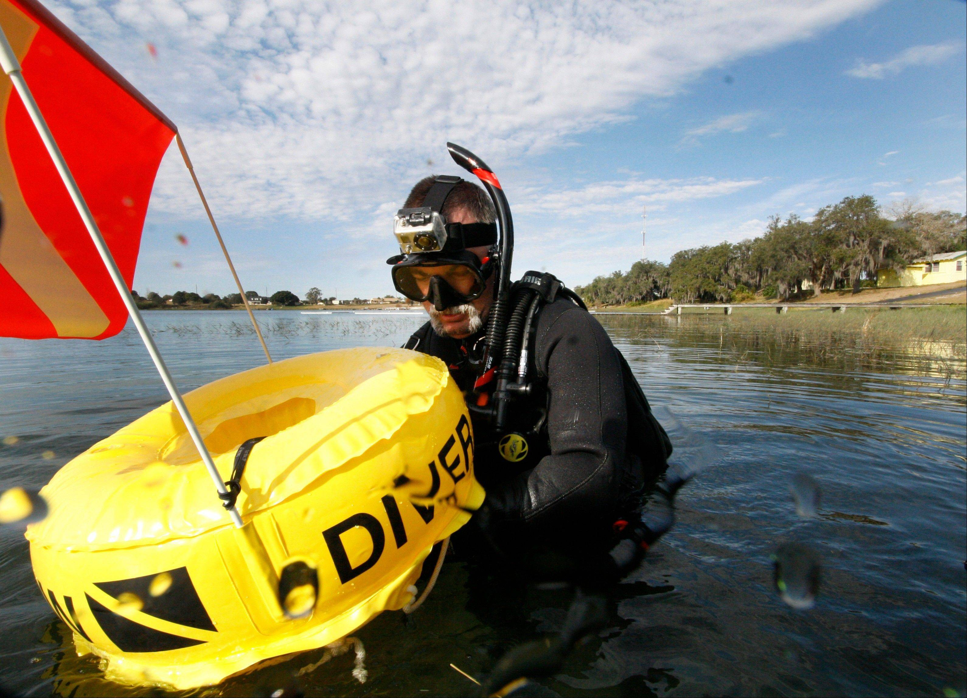"Kenny Jenkins hooks a line to a float with a ""Diver Down"" flag as he prepares to place a geocache."