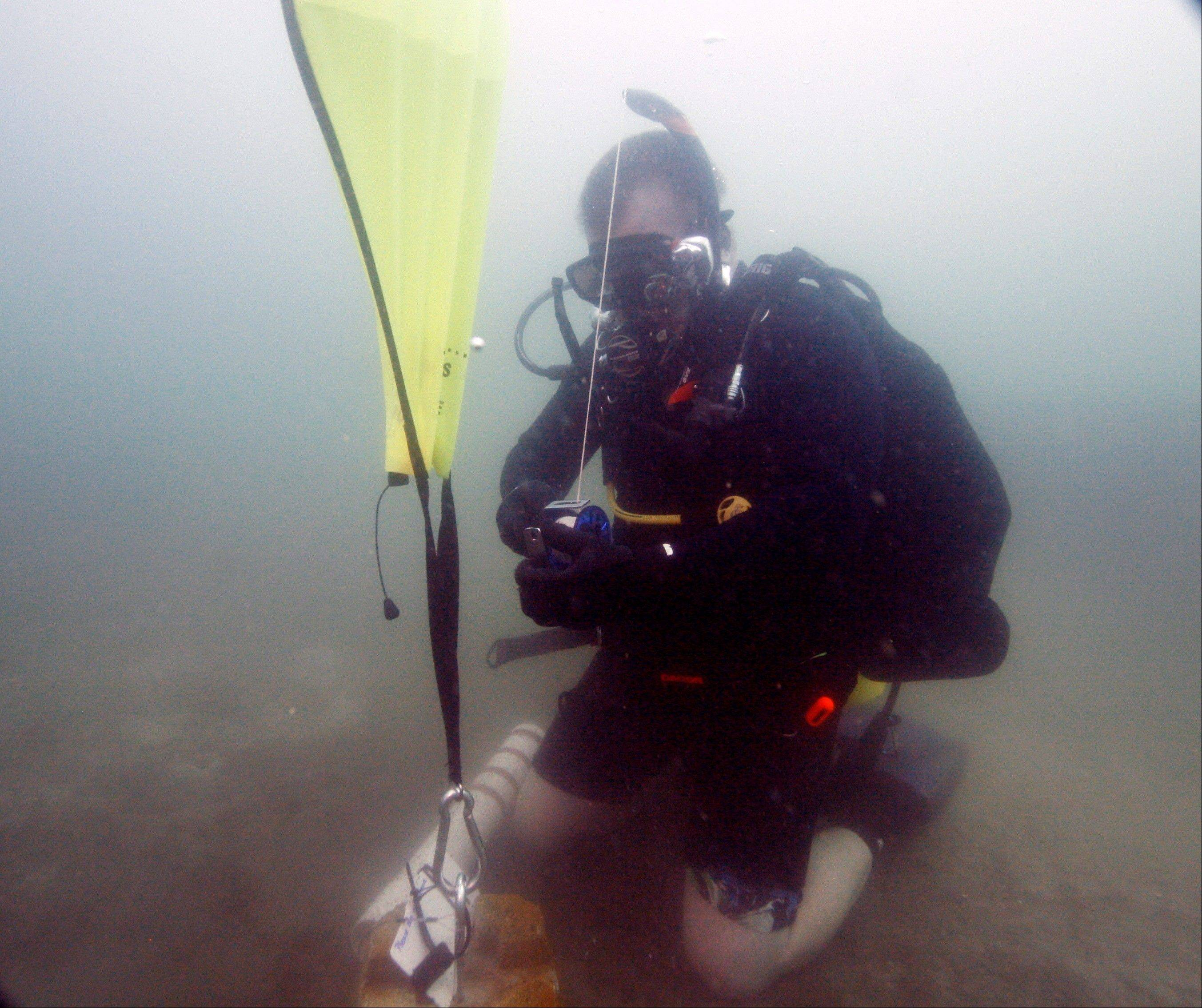 Kenny Jenkins uses a lift bag to place a weight and geocache marker. About 100 geocaches around the world today are only accessible with scuba gear, according to the geocaching.com database.