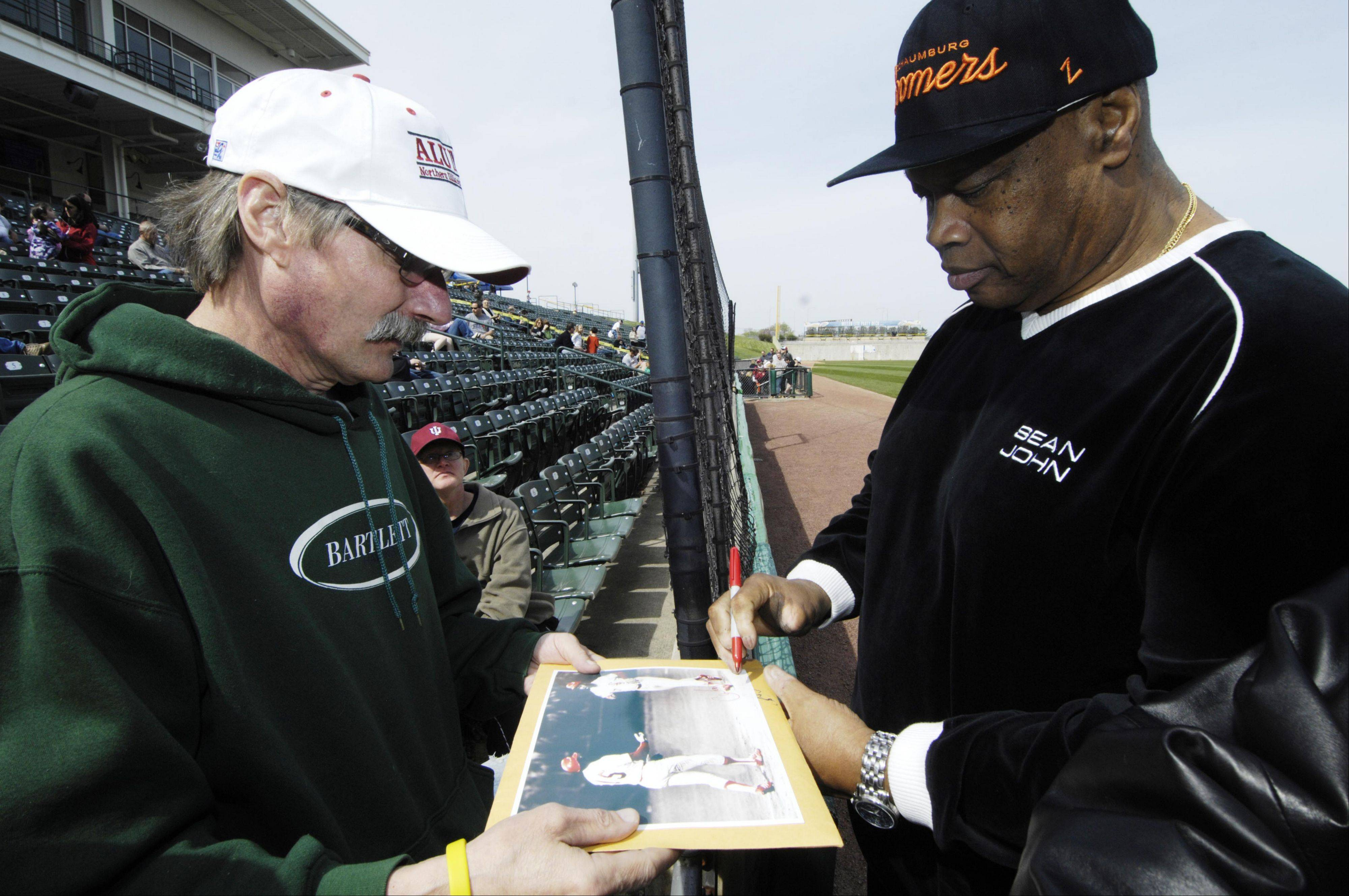 Following his introduction as a Boomers coach, Carlos May signs a photo of himself from his days as a White Sox player for Ken Skelnik, left, of Bartlett, during the Schaumburg Boomers baseball team open house Saturday.