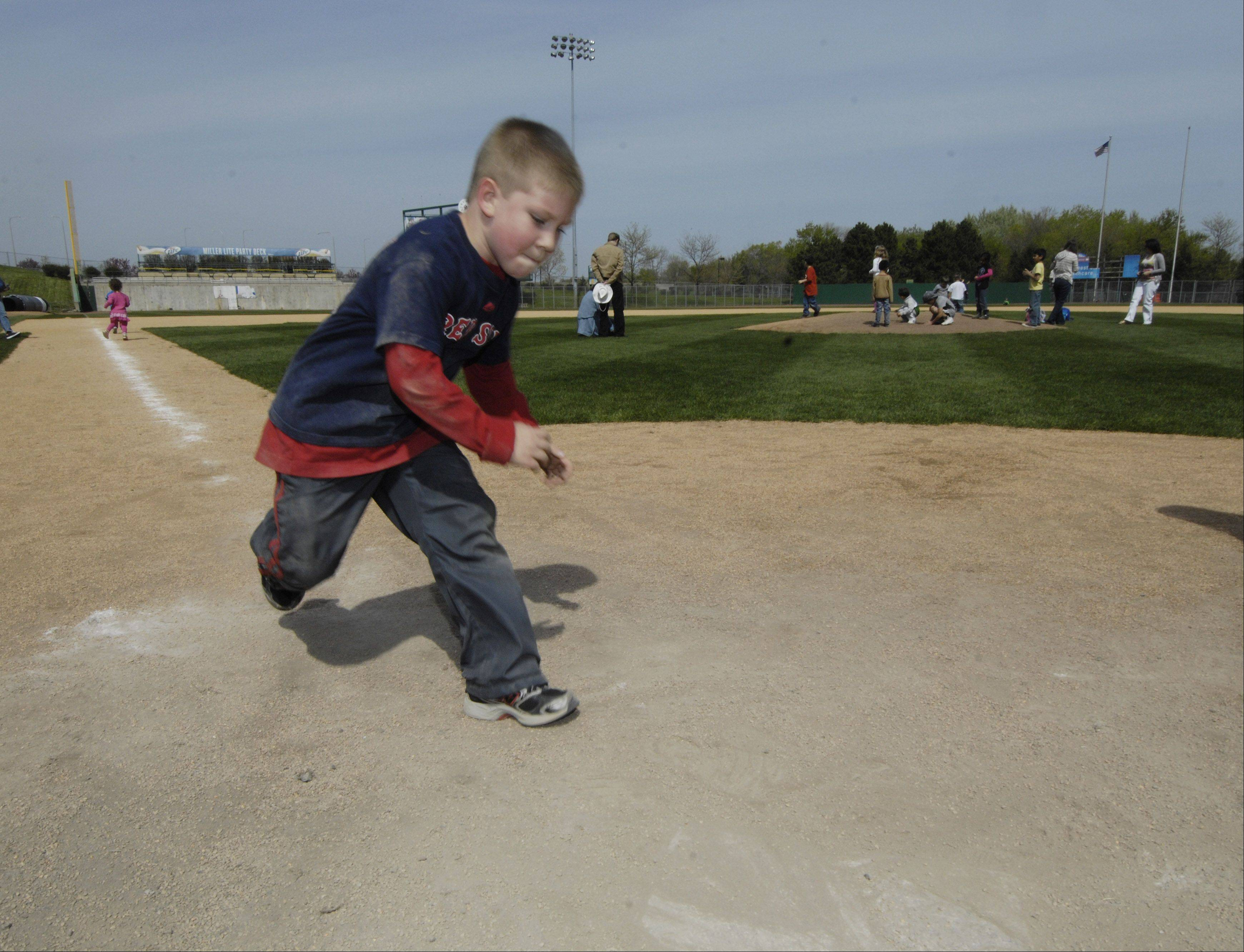 Ryan Mc Grew, 5, of South Elgin tumbles into home plate after running the bases during the Schaumburg Boomers baseball team open house Saturday.