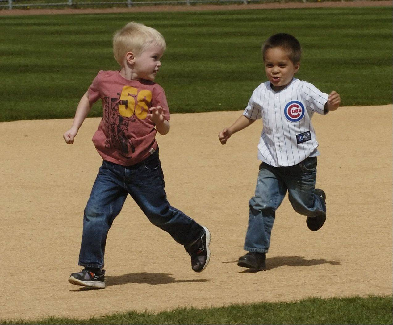 Ben Lukes, 4, of Bloomingdale, left, and his friend Maximilian Alvarado, 4, of Itasca, run the bases during the Schaumburg Boomers baseball team open house Saturday.