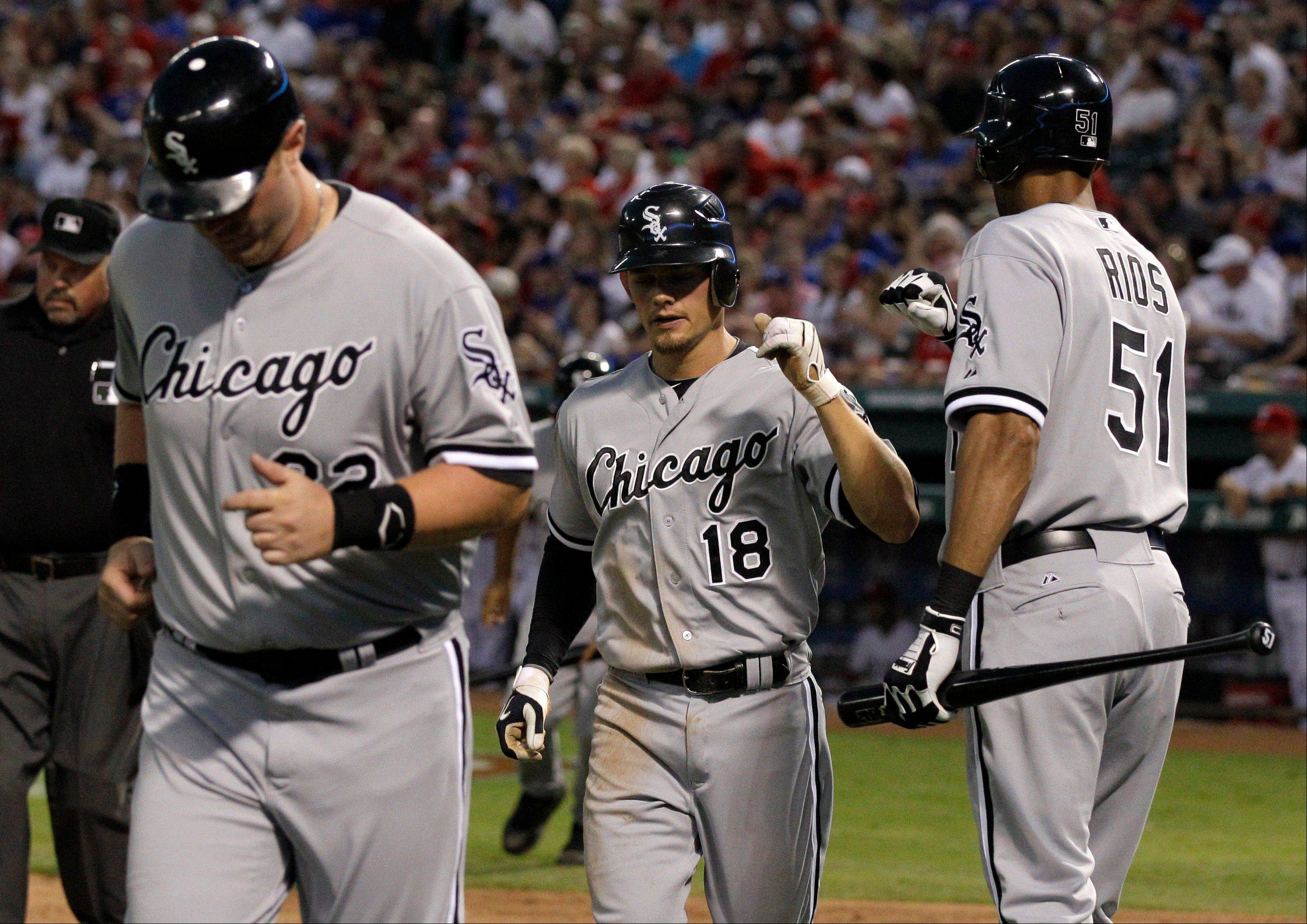 White Sox designated hitter Adam Dunn and Brent Lillibridge are congratulated by Alex Rios Saturday after the two scored on a Paul Konerko double in the third inning.