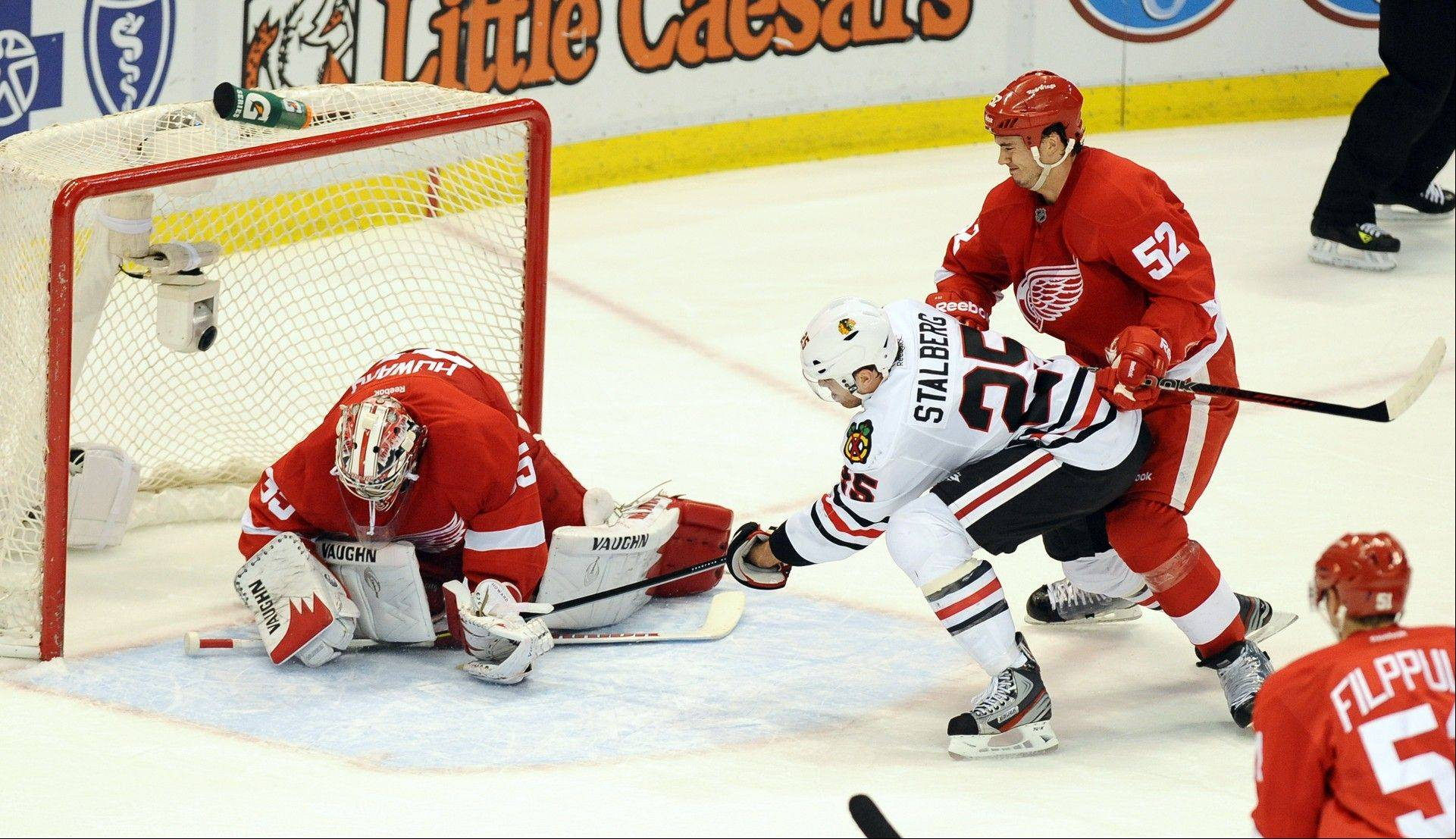 Detroit Red Wings goalie Jimmy Howard, left, snuffs a shot by the Blackhawks Viktor Stalberg Saturday during the second period. The Blackhawks won 3-2 in a shootout.