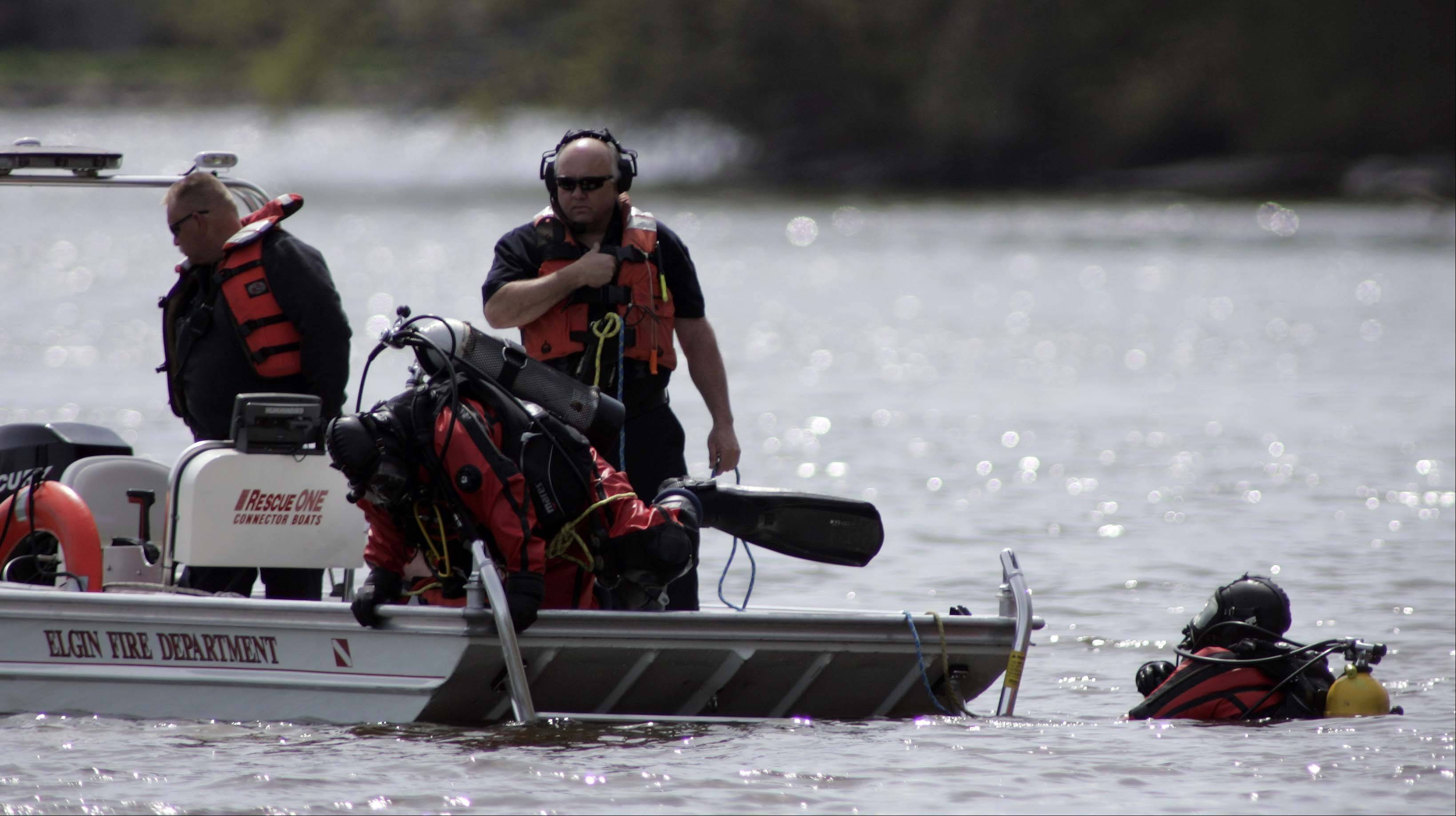 Elgin rescue personnel search the Fox River Saturday after a fisherman almost ran into a submerged car in the river just south of Continental Baseball fields in Elgin.