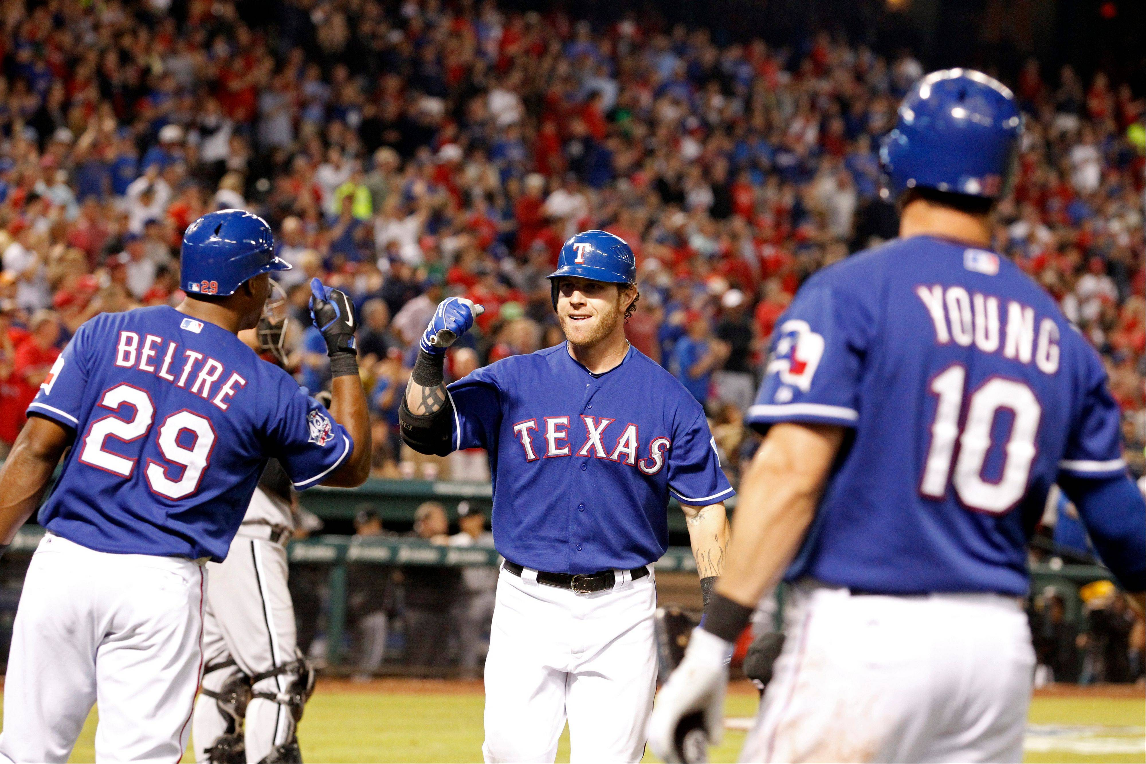 Texas Rangers Josh Hamilton, center, celebrates with teammates Adrian Beltre (29) and Michael Young (10) Sunday after he hit a home run in the sixth inning against the White Sox.