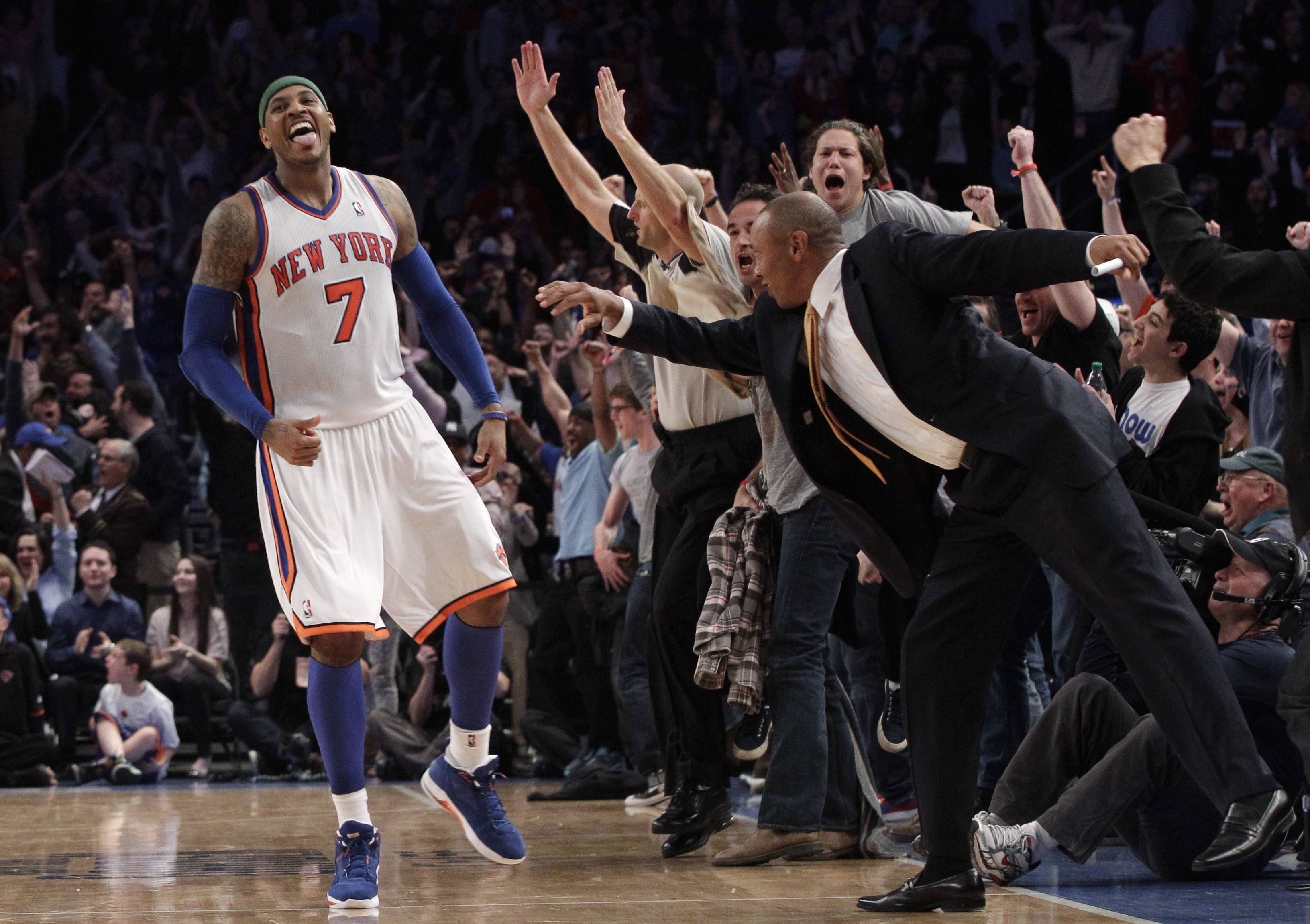 New York Knicks forward Carmelo Anthony and fans react after Anthony hit a 3-pointer in the closing seconds of overtime Sunday against the Bulls.