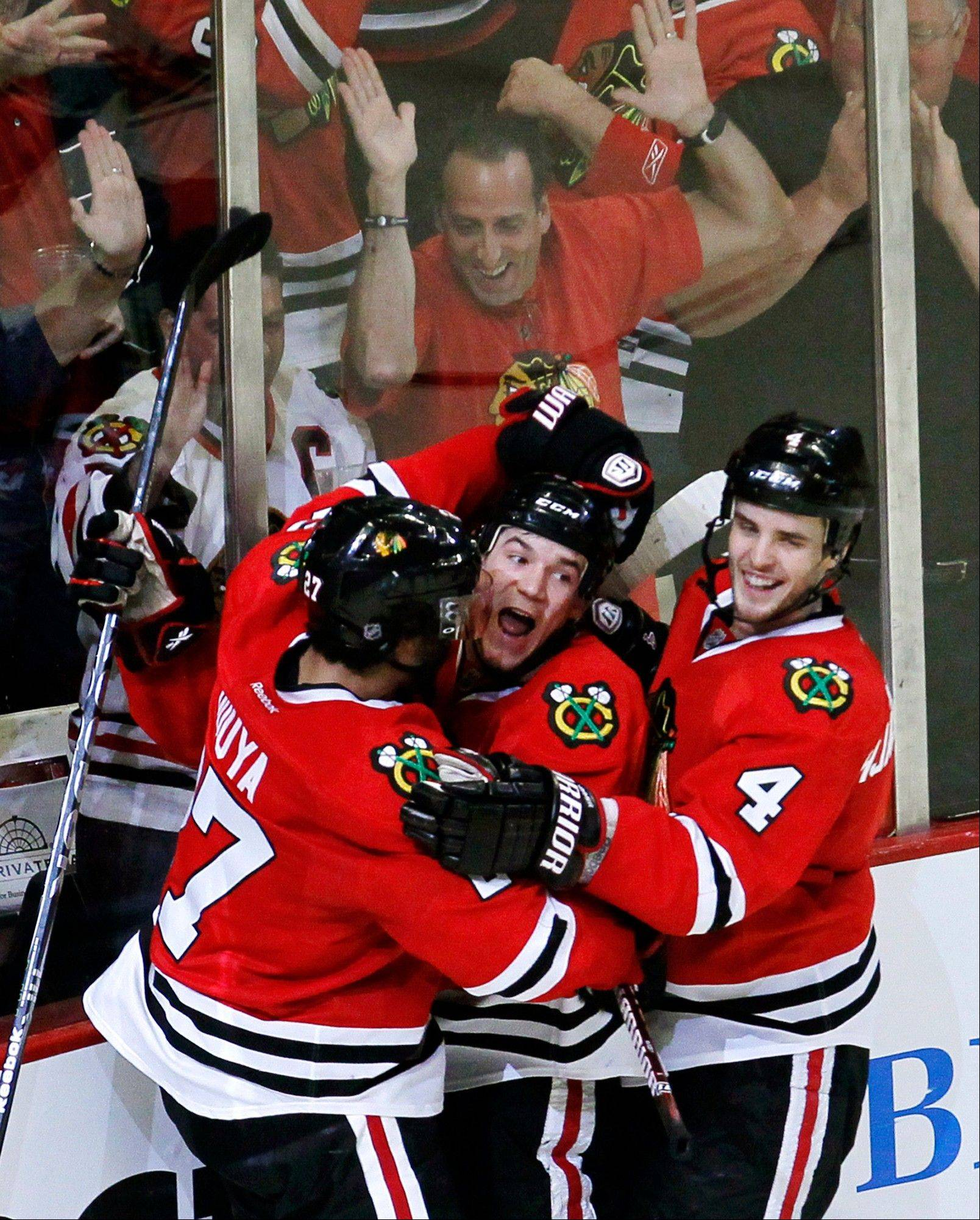 Defenseman Johnny Oduya (27) and defenseman Niklas Hjalmarsson (4) celebrate with Andrew Shaw after Shaw's game-winning overtime goal against the Vancouver Canucks on March 21.