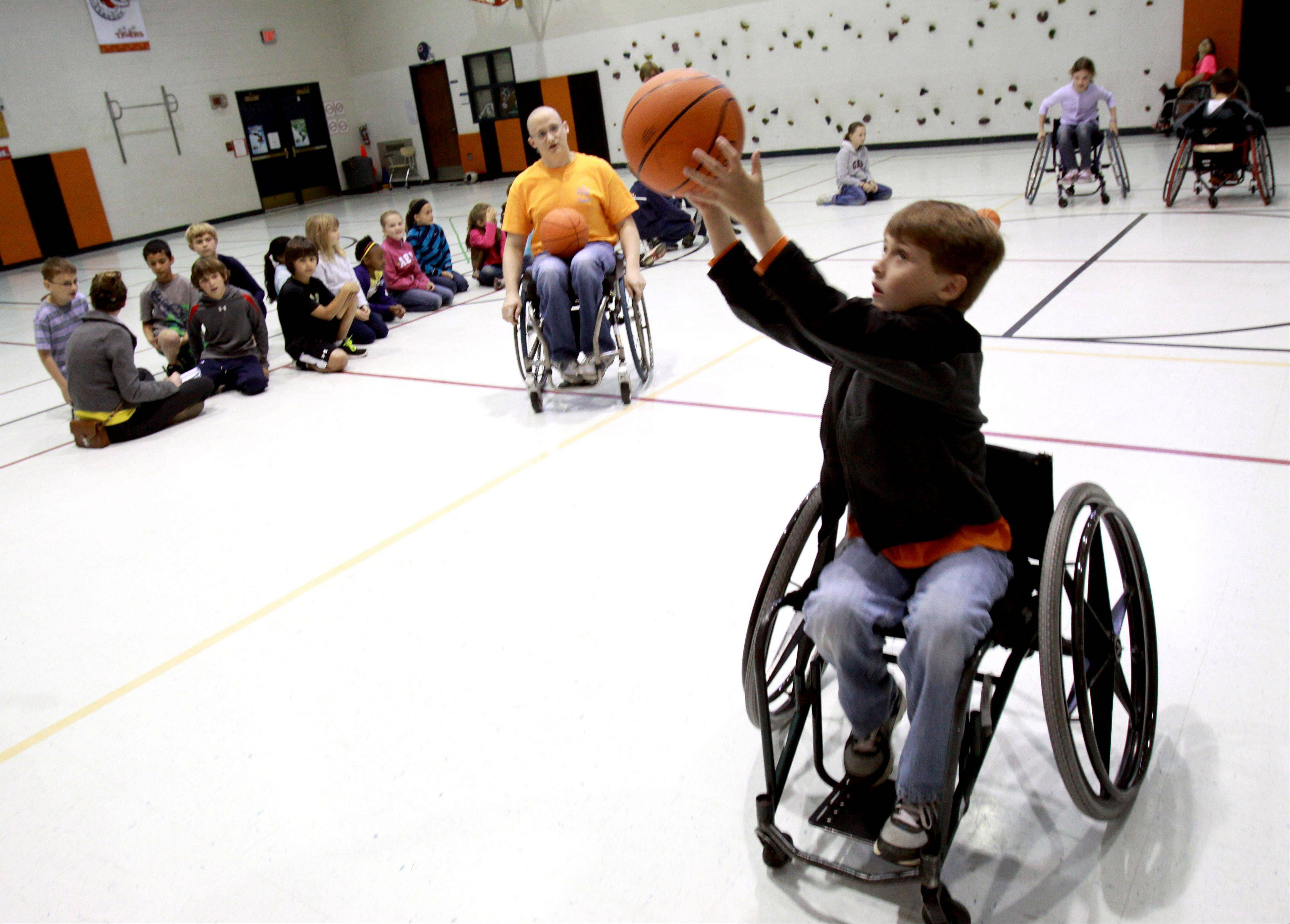 The Western DuPage Special Recreation Association's Disability Awareness Program visits Wiesbrook School in Wheaton, where third-grader Matt Dale tries out wheelchair basketball coached by Kevin Hosea, left, adapted sports supervisor with WDSRA.