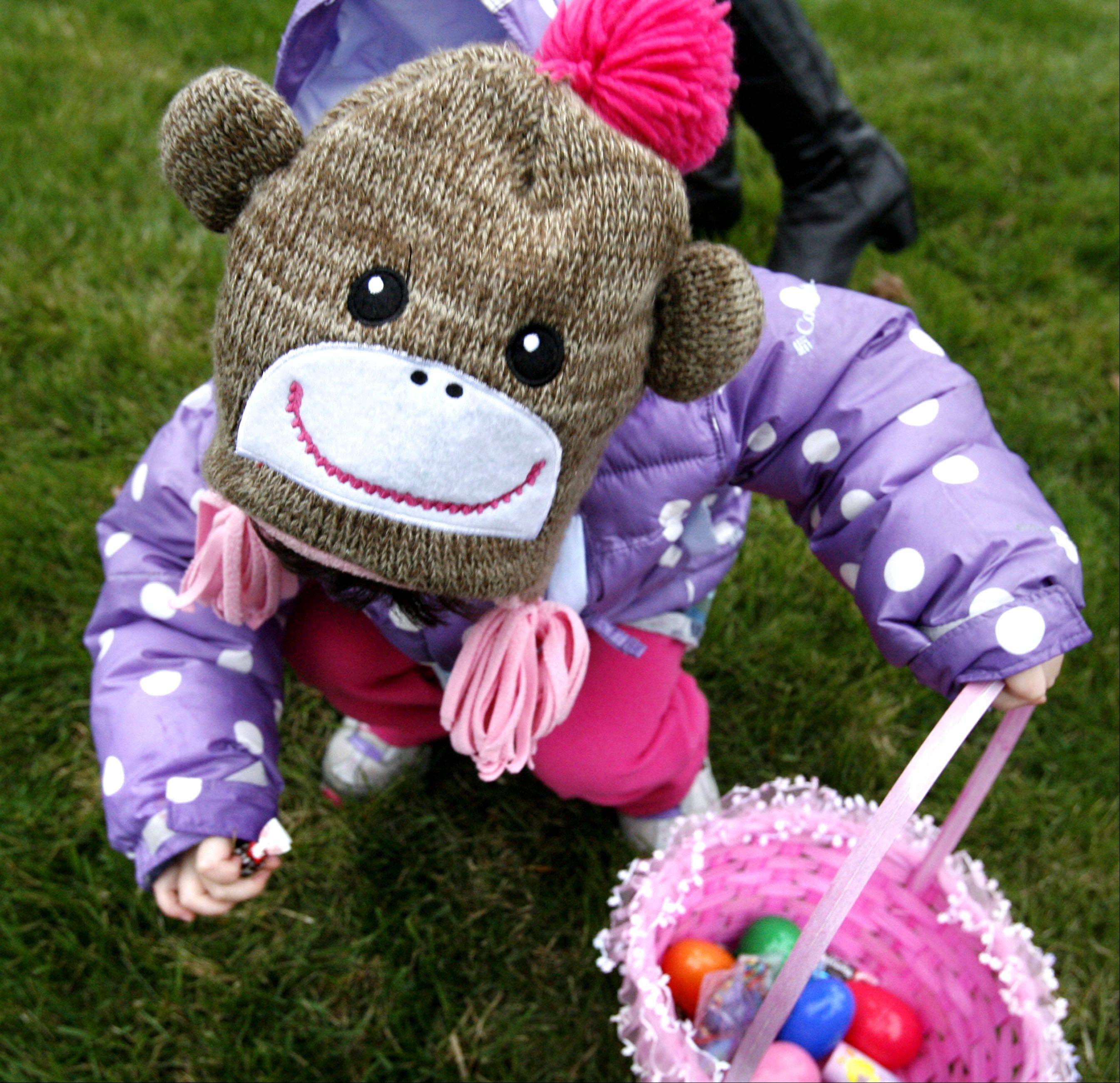 Emily Cheug, 3, of Mundelein, wearing a winter monkey hat picks up candy and filled plastic eggs at Wauconda Park District's annual Easter egg hunt at Cook Park on Saturday, March 31st.