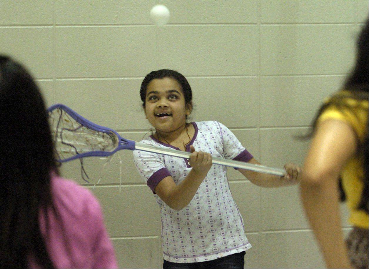 Nikki Patel tries to catch the ball with her stick during a hands-on Lacrosse demonstration for Hawthorn Elementary North fifth graders. Lynn Merrill of the Illinois Girls Lacrosse Association gave a presentation Tuesday.