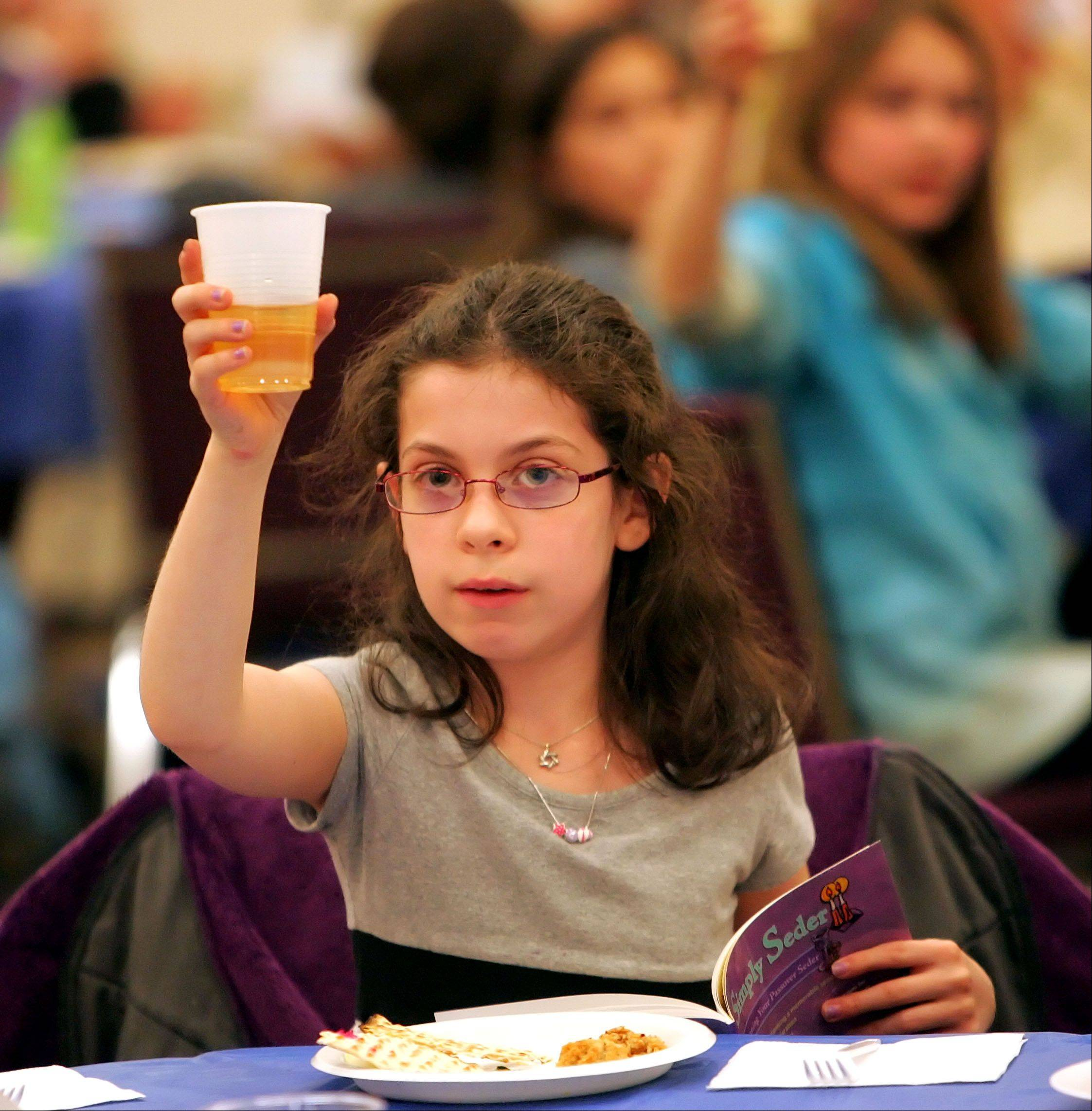9-year-old Deena Dobrin of Libertyville holds up a glass of white grape juice symbolizing wine as Congregation Or Shalom in Vernon Hills held a model Seder for kids in grades 3-5 Wednesday in Vernon Hills.